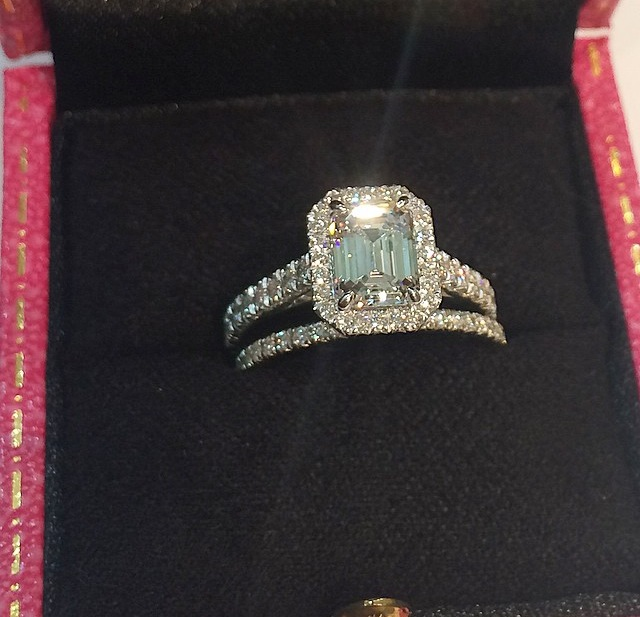 Look at how the light reflects on the step-cut facets of this stunning colorless emerald cut diamond. The round brilliant diamond halo is the perfect contrast. Feminine, timeless + sophisticated.