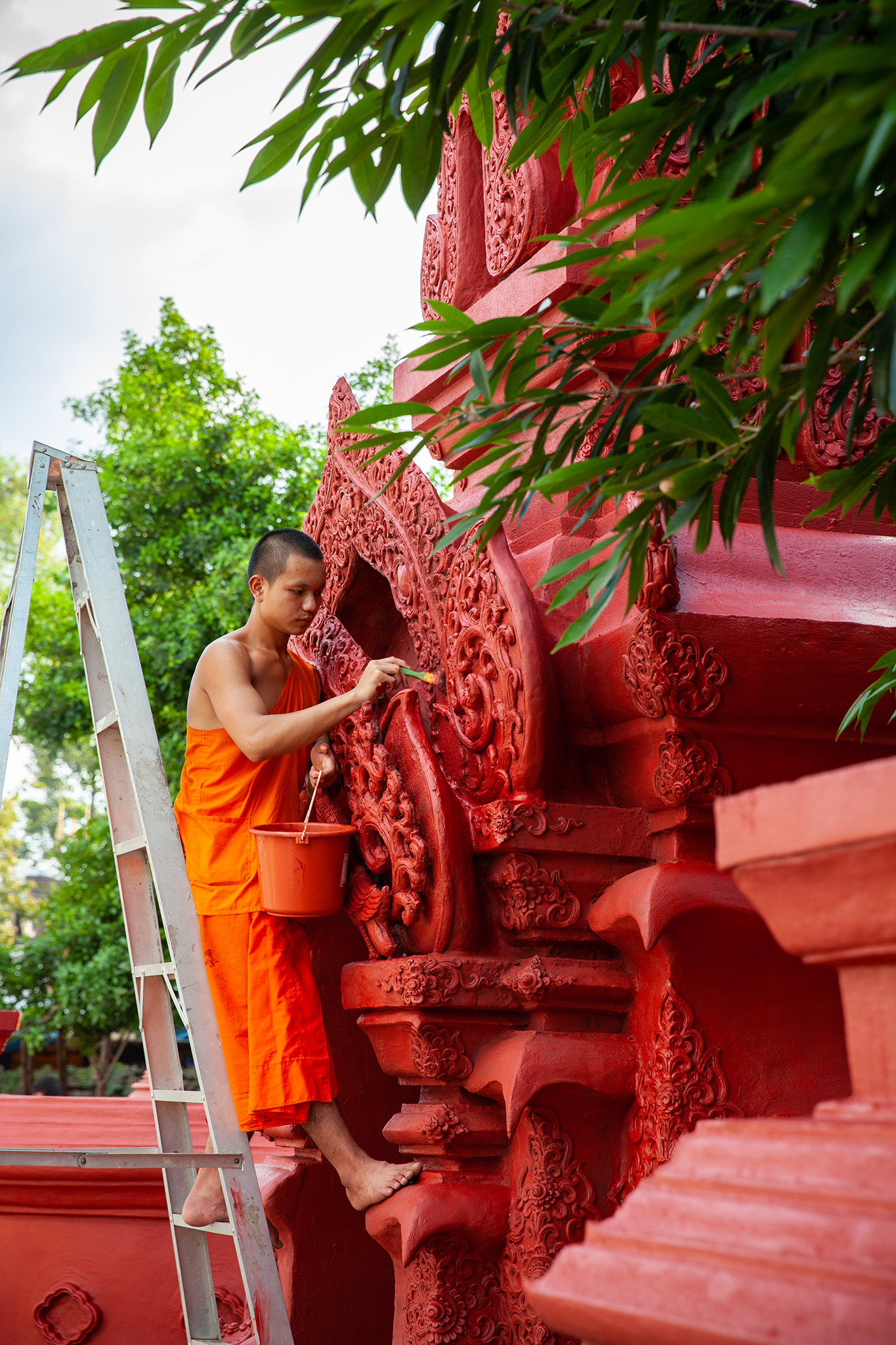 a young monk touches up the paint at Wat Chedi Luang
