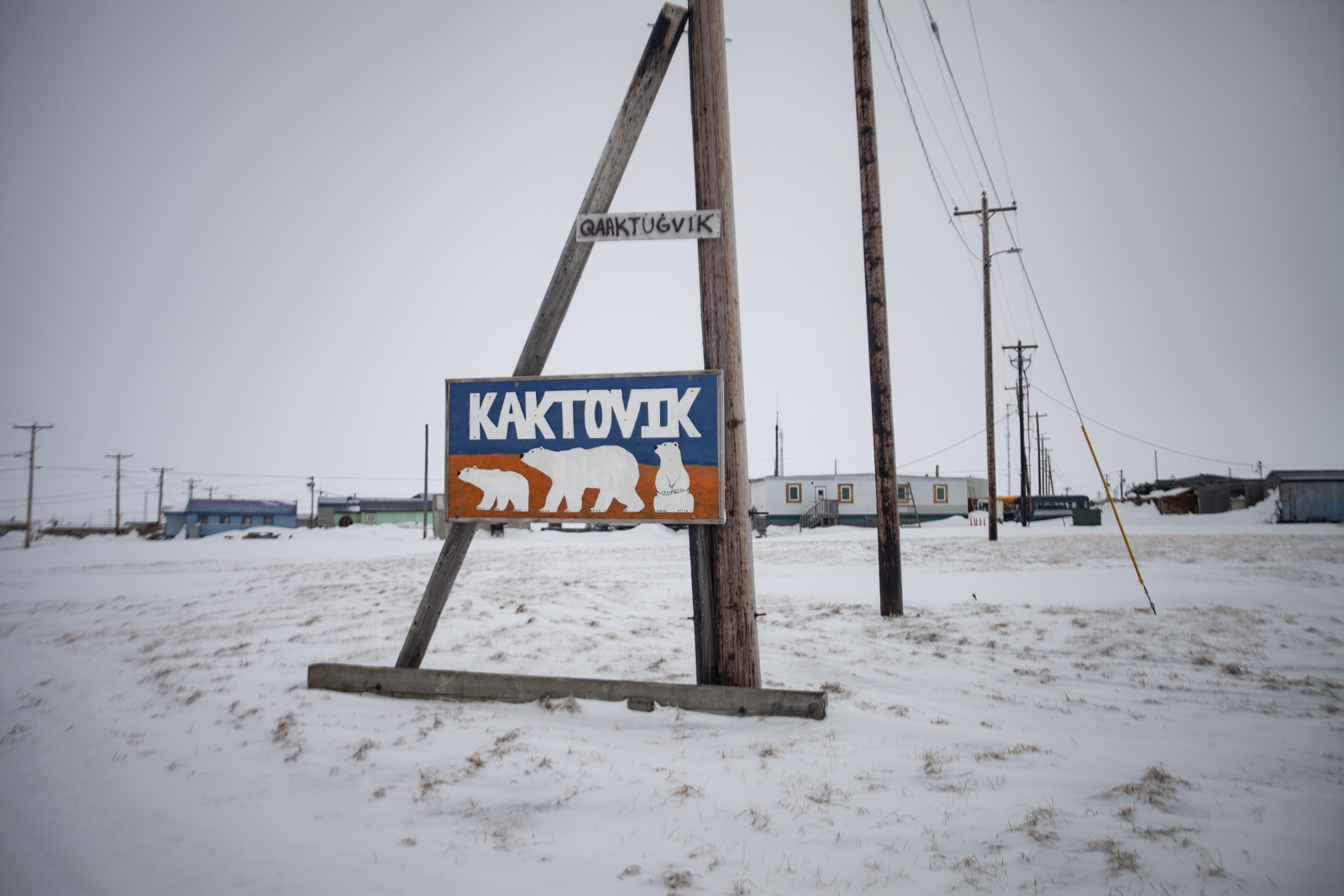Sign at the edge of town which includes an alternate spelling: Qaaktugvik