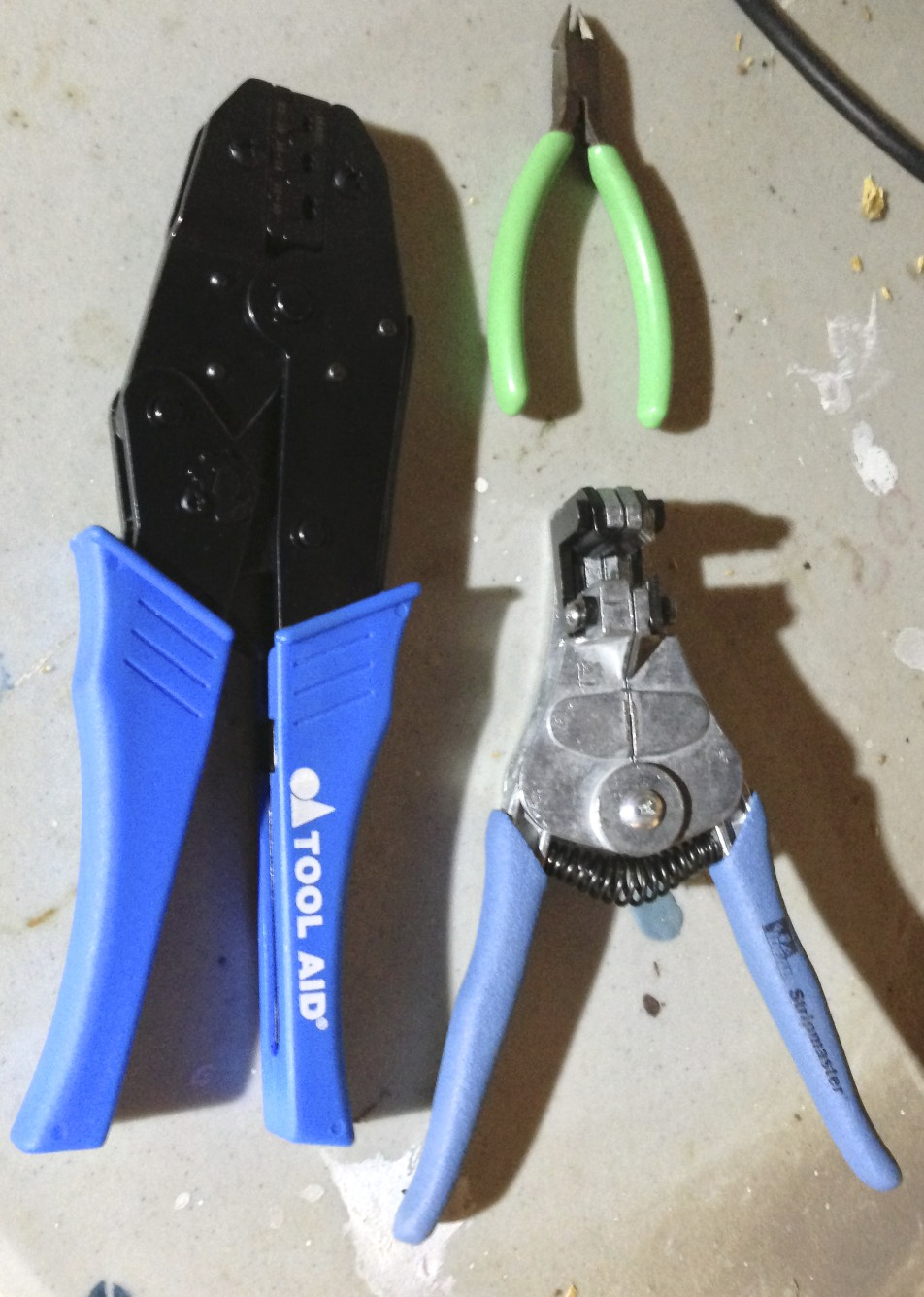 A ratcheting open barrel crimp tool (left). wire cutters (top) and wire strippers (bottom).