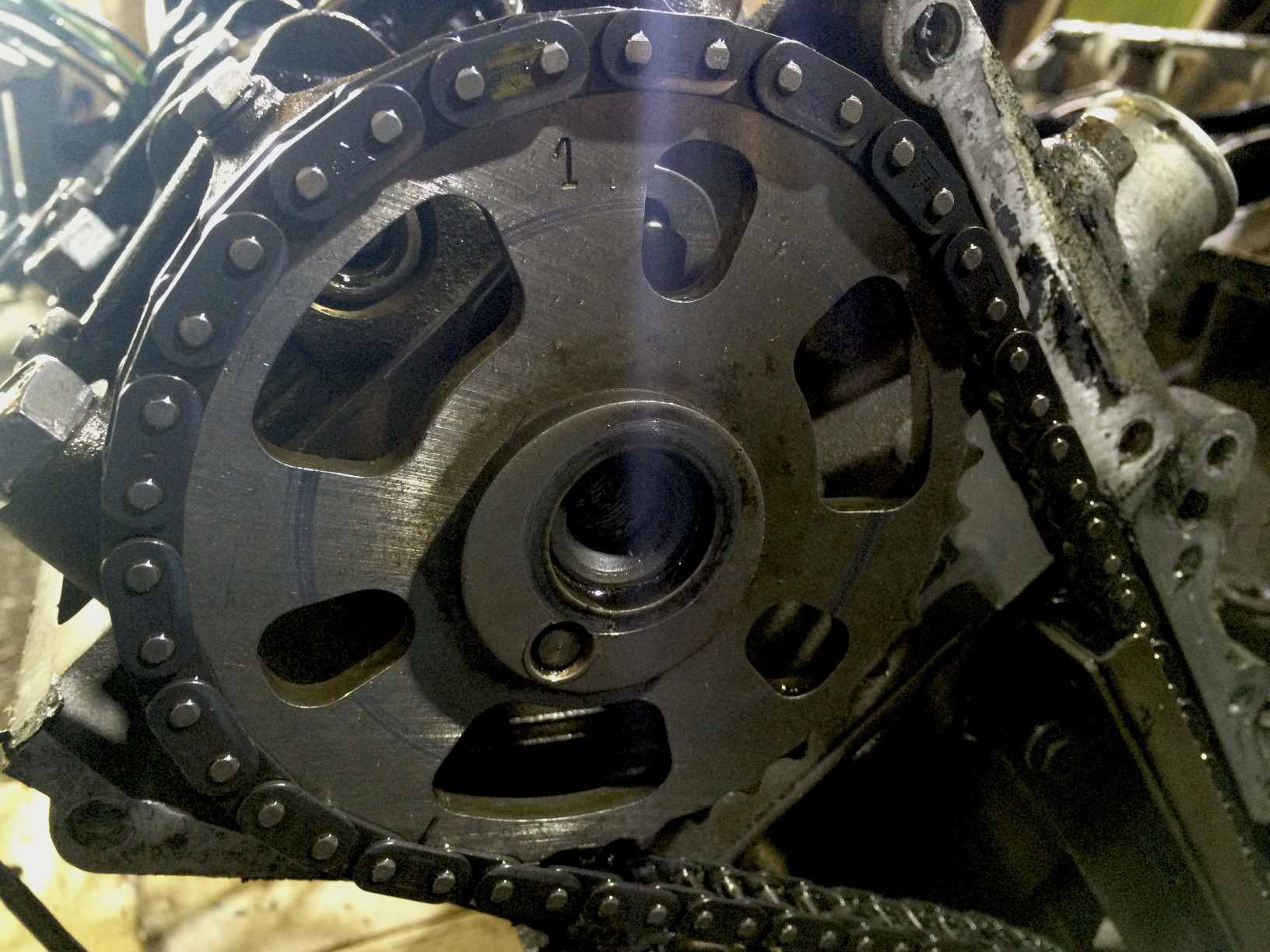 The timing chain on the sprocket, but with the hex screw removed. The '1' at the top of the sprocket lines up with the yellow mark on the timing chain when the engine is properly timed, The pin below the center hole lines up with a recess in the cams and keeps the sprocket locked with the cams' rotation.