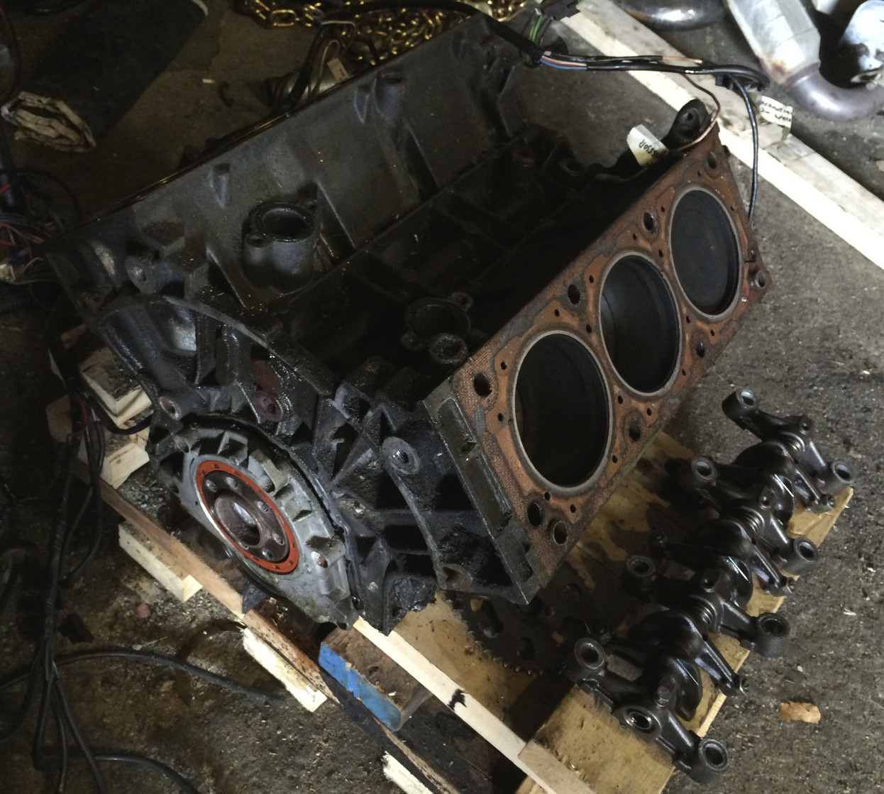 Block with the cylinder heads removed. A set of rocker arms is sitting on the pallet to the right of the block.