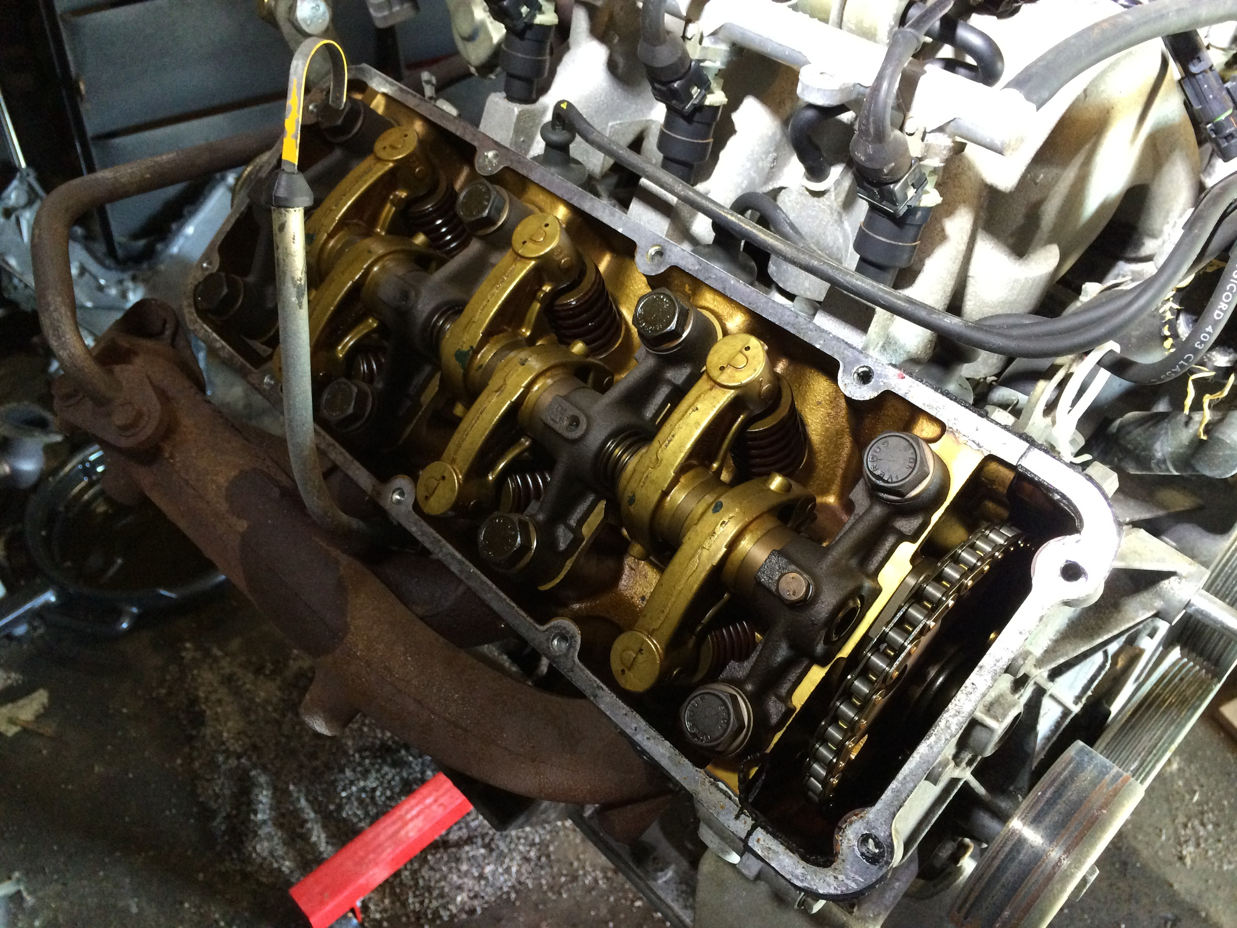 The valve train is revealed once the cylinder heads are removed. The rocker arms have a golden color, while the 2.8L engine has black rocker arms.