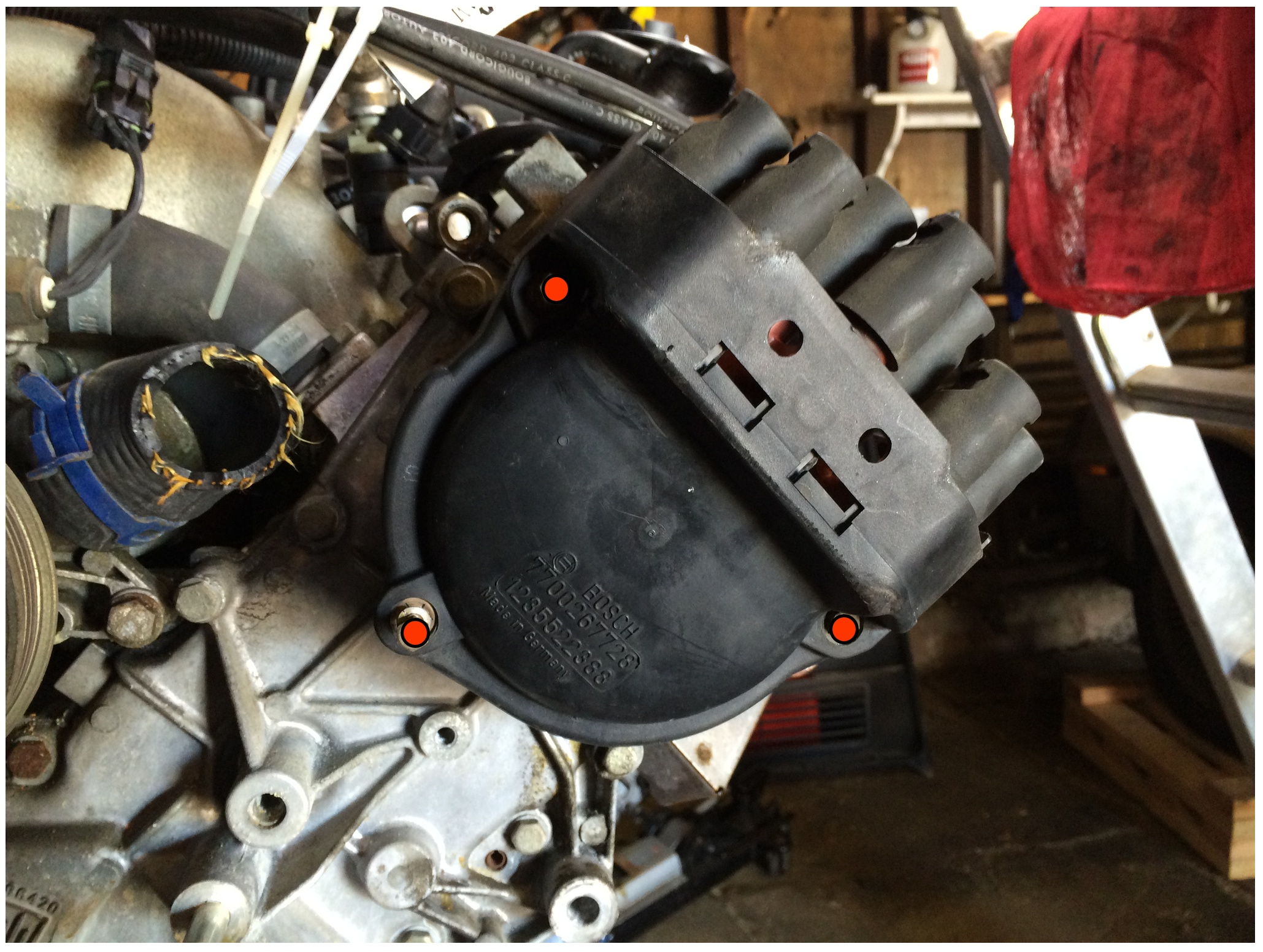 """The three red dots mark the nuts for the distributor cap. These can be removed with a 7mm or 5/6"""" socket."""