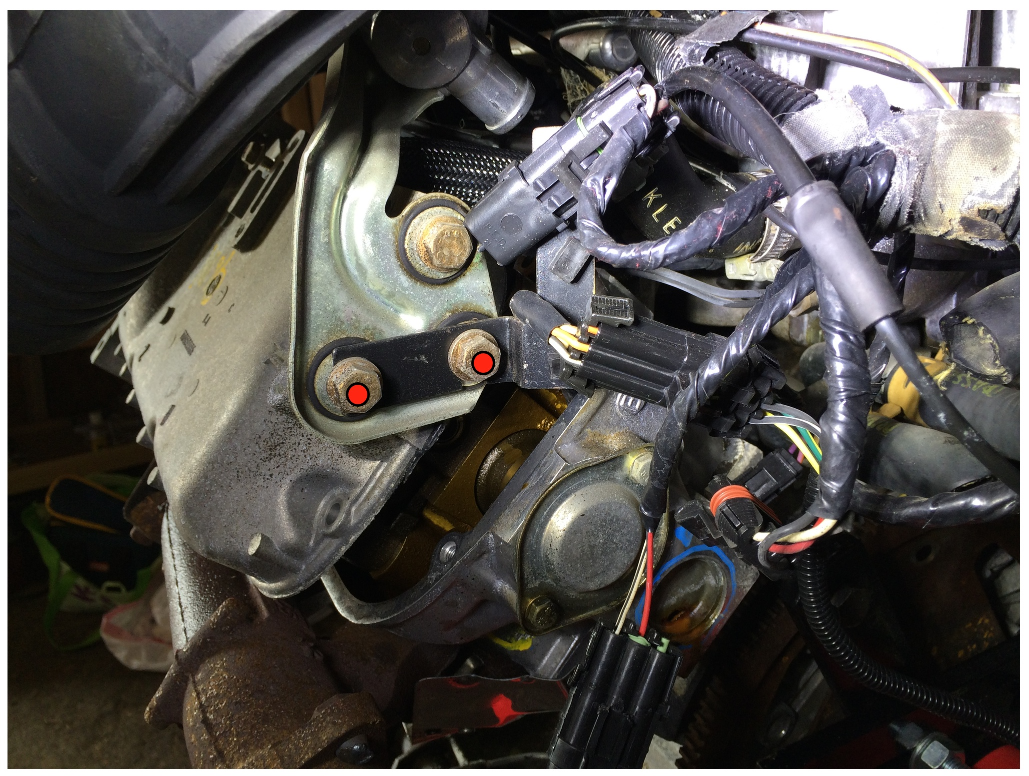 The cold air temperature sensor is mounted on the back of the head, and can be removed by taking out the two nuts marked in red with a 13mm socket. I had already taking out the valve cover heads before realizing the harness was there.