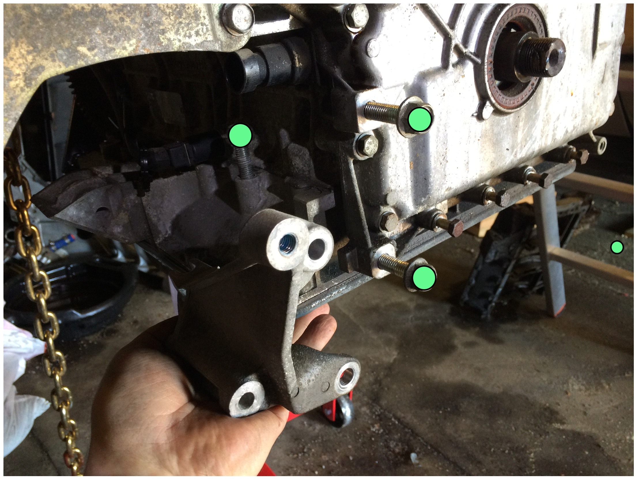 Three bolts (green, 15mm socket) hold a bracket to the bottom of the engine.