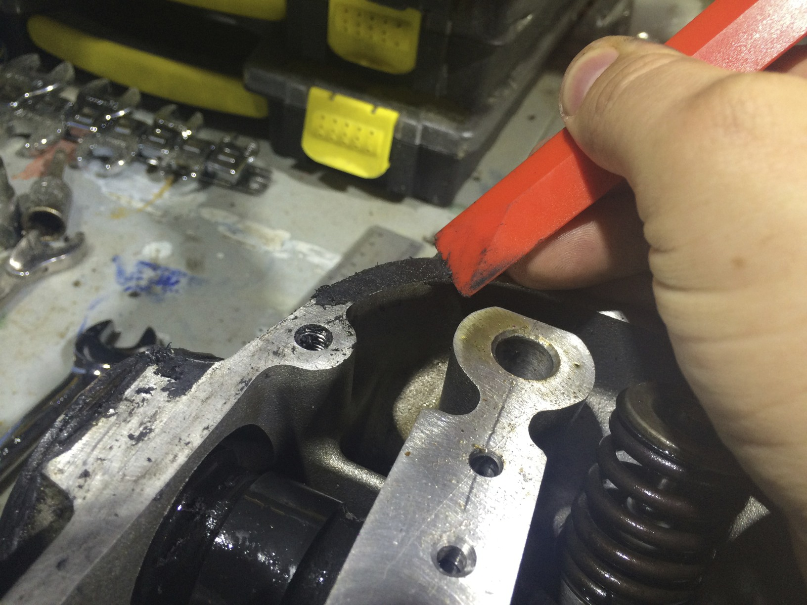 Using a composite/plastic scrapper to remove the remnants of a gasket from a cylinder head.