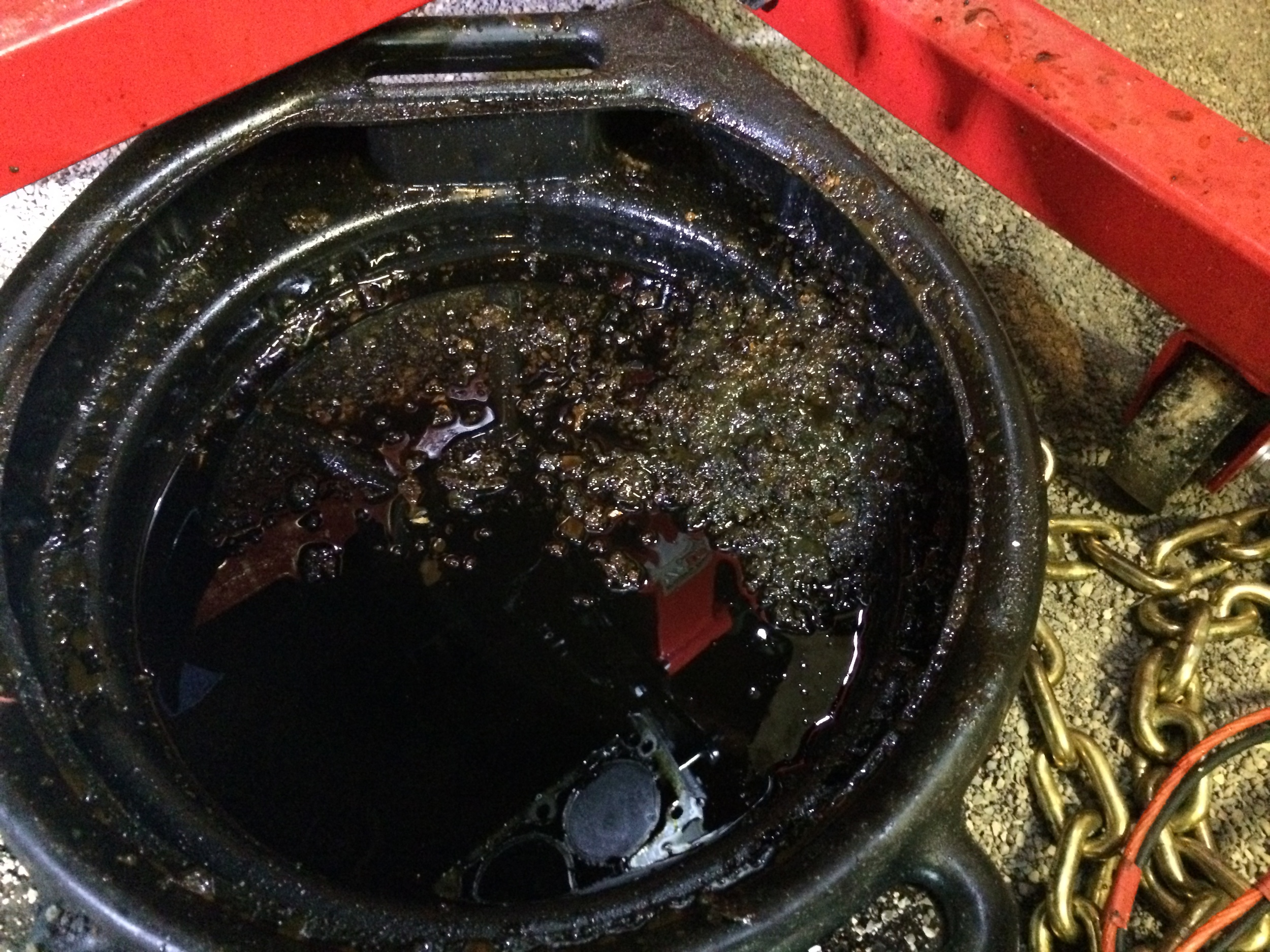 Mud that was pulled out with the pick was deposited in an oil pan. This was from only one side of the engine, and it was still quite dirty.