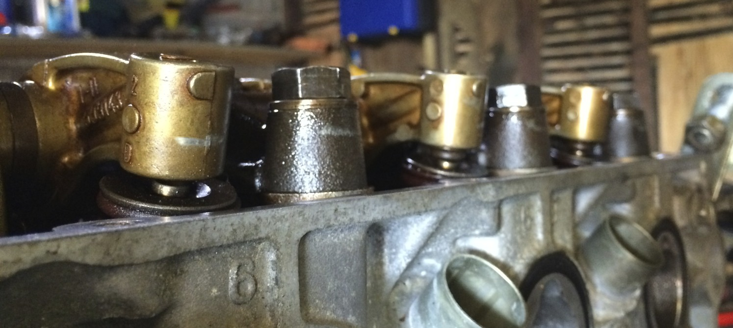 The gap between the leftmost finger and the valve stem shows where I didn't notice one of the tappets slip out. You can see the tappet sticking out from under the other two fingers.