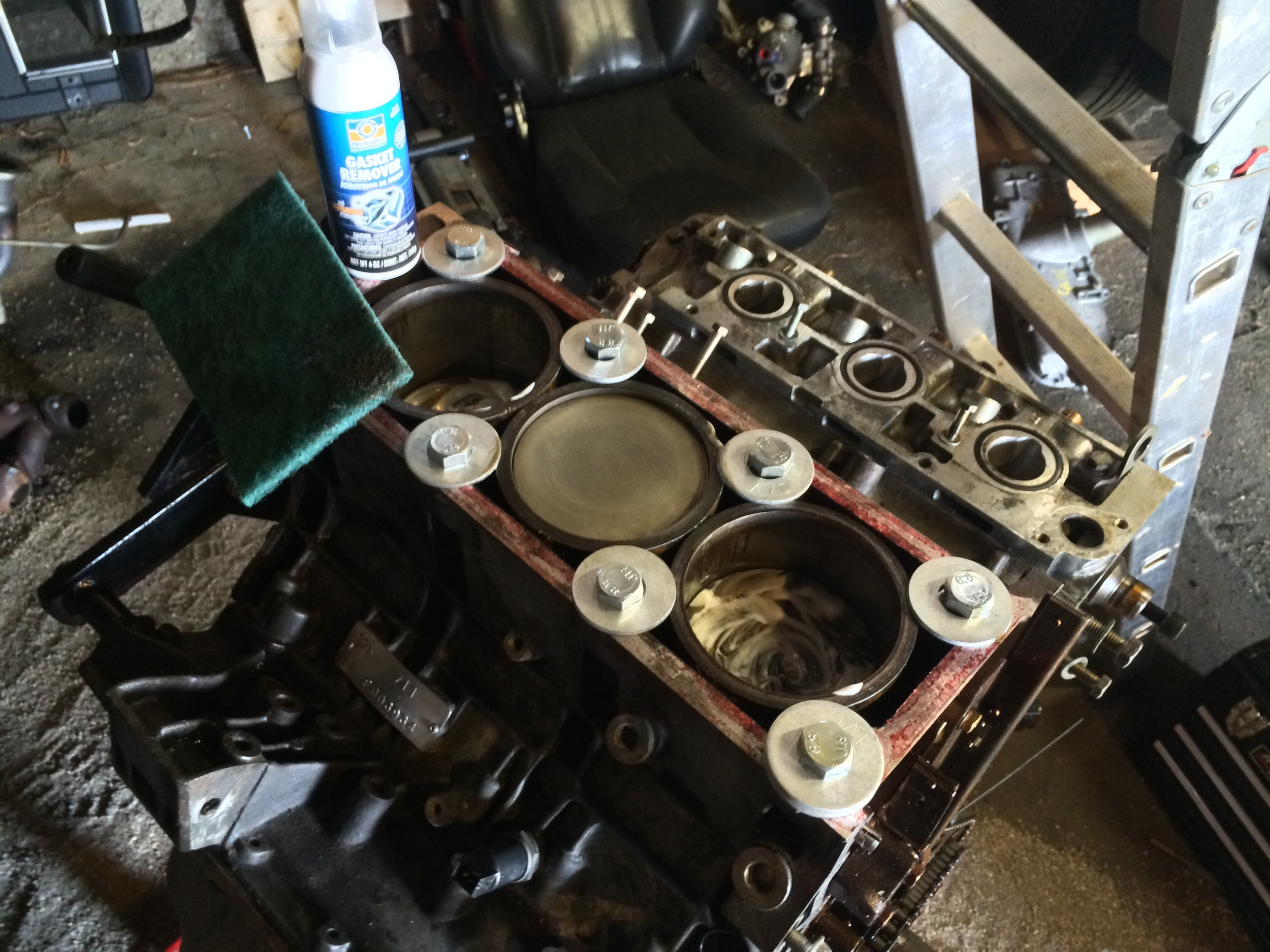 The cleaned-up center piston, and two dirty pistons, along with the Permatex Gasket Remover and a scrubbing pad.