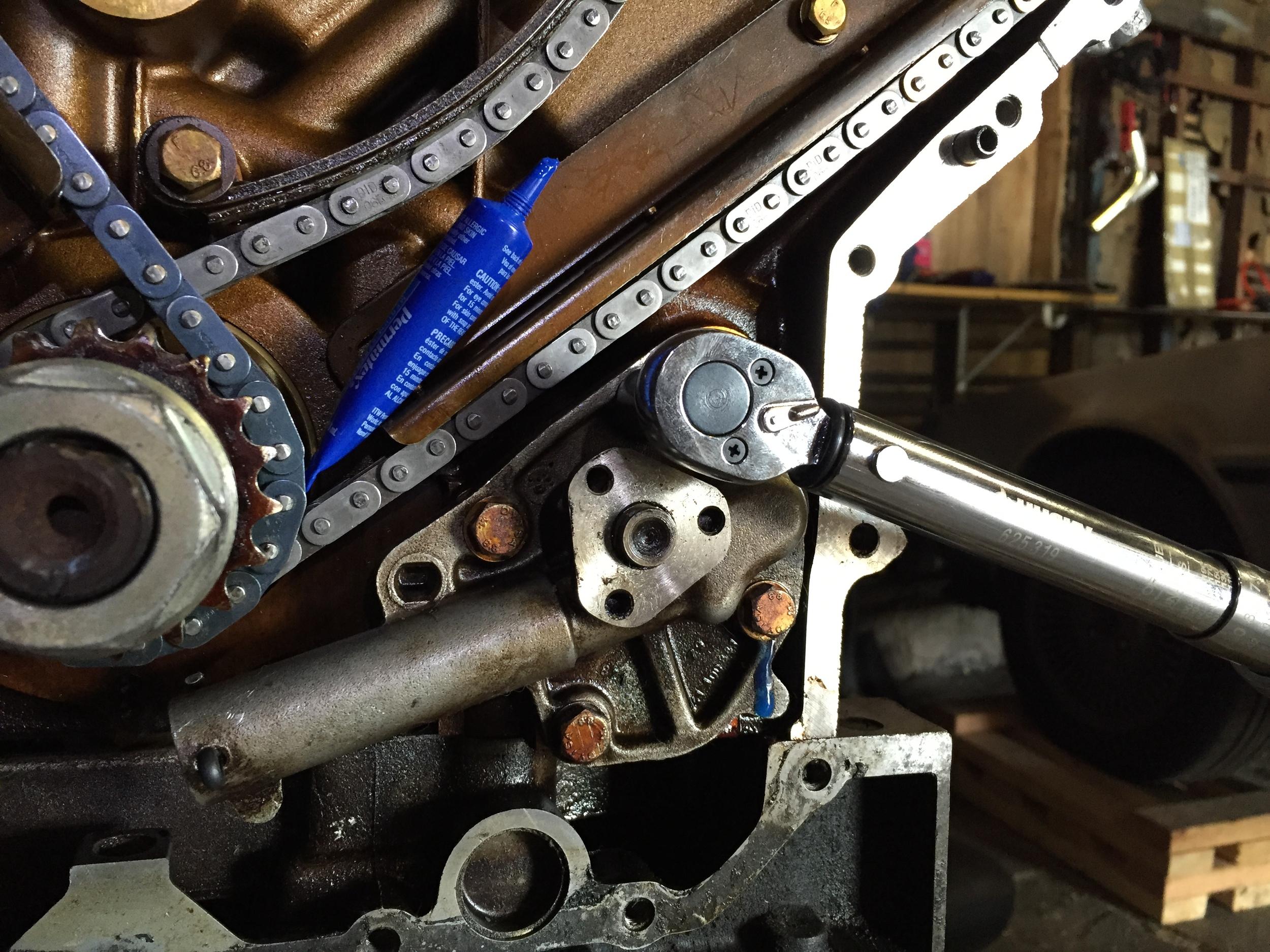 Torquing down the oil pump. The tube of blue LockTite can be seen resting on the chain guide,