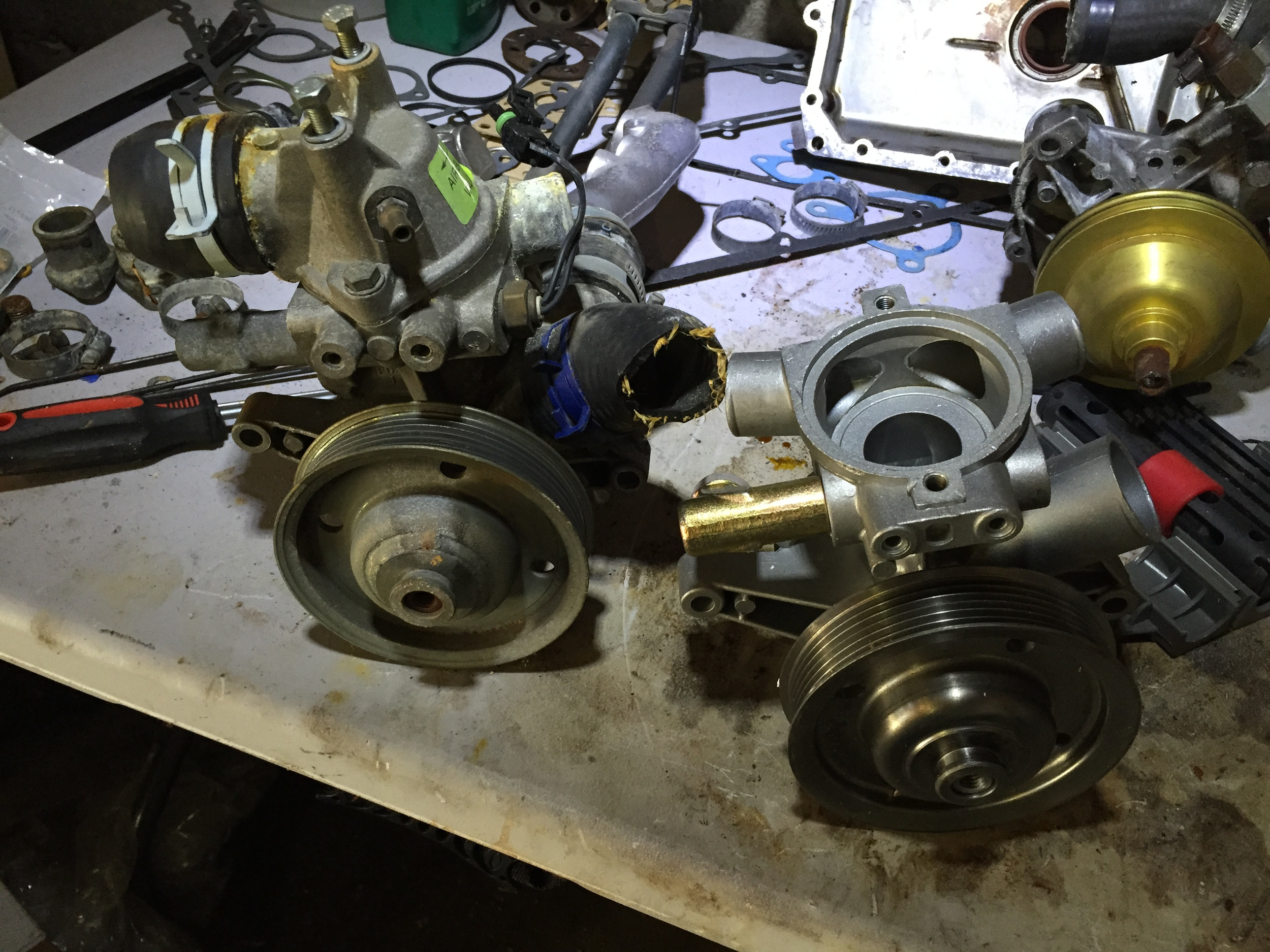 The old 3.0L pump (left) and the new one (right); the 2.8L pump is visible in the background.