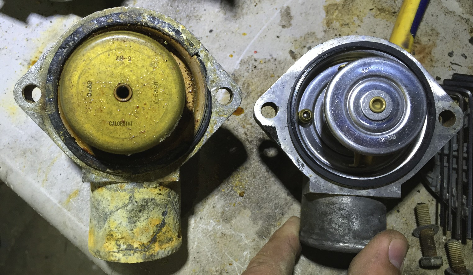 The extremely dirty 3.0L thermostat and housing (left) and the clean 2.8L thermostat (right).