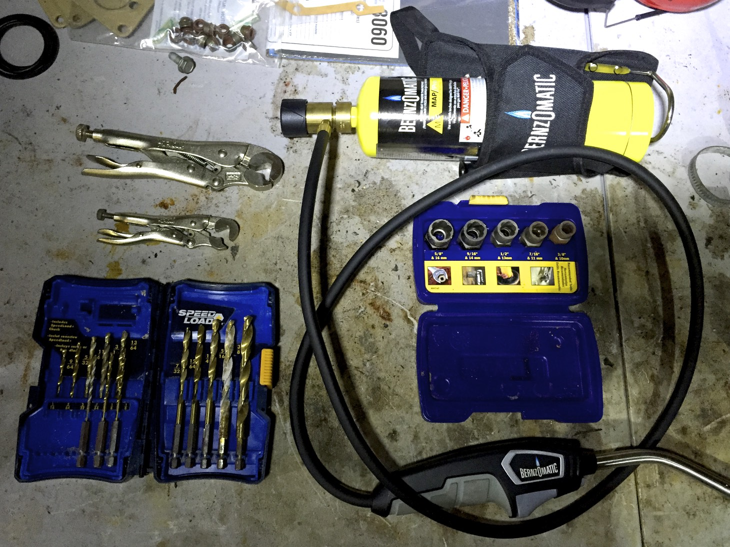 Some bolt removal tools: bolt vice grips (top left), drill bits (bottom left), a MAP torch (top right), and bolt grip extractors (middle right)
