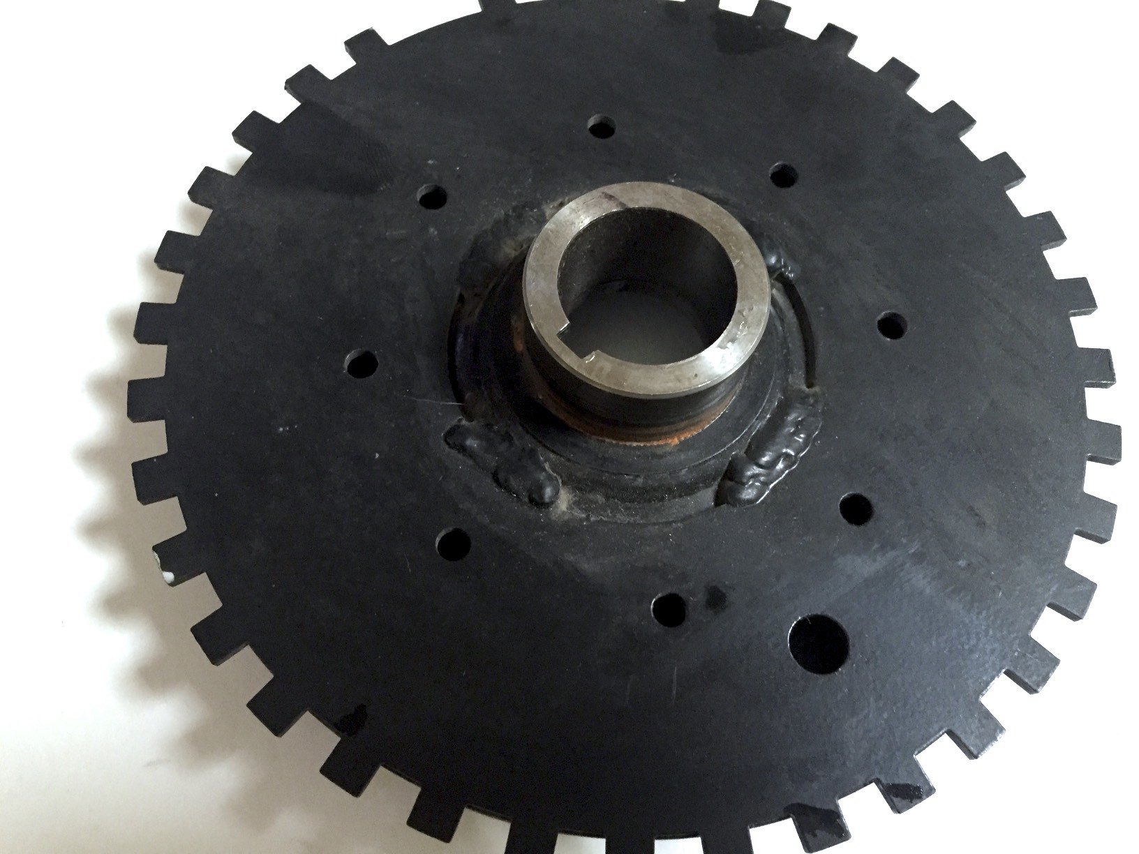 The back of the pulley, with the gear tack-welded in four places. The missing tooth is visible near the top of the image.