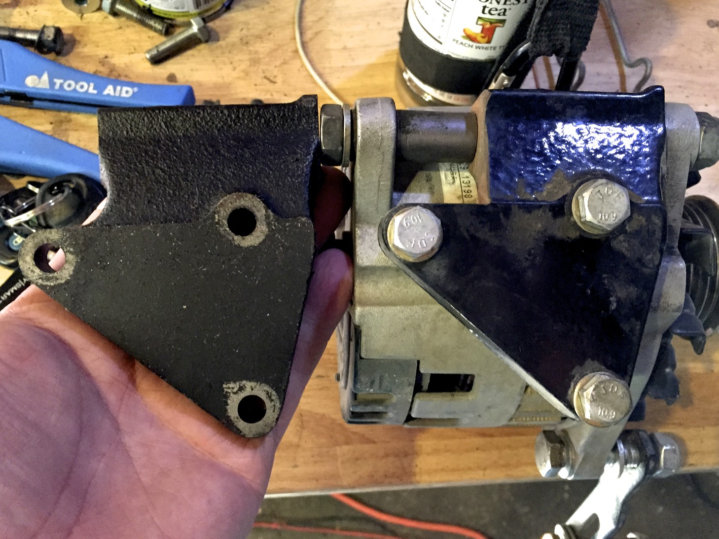The original (left) and modified (right) brackets. If you look carefully you can see that where the long bolt goes through the bracket from the alternator is shorter on the modified one.