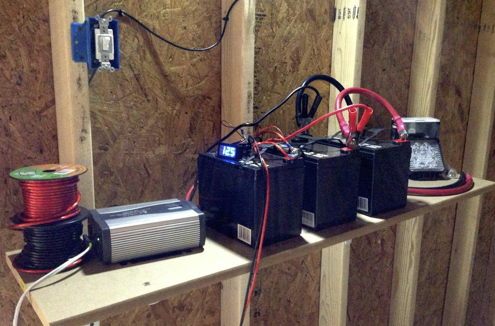 The batteries hooked up to each other, a power inverter (grey box on the left) and a some worklights.
