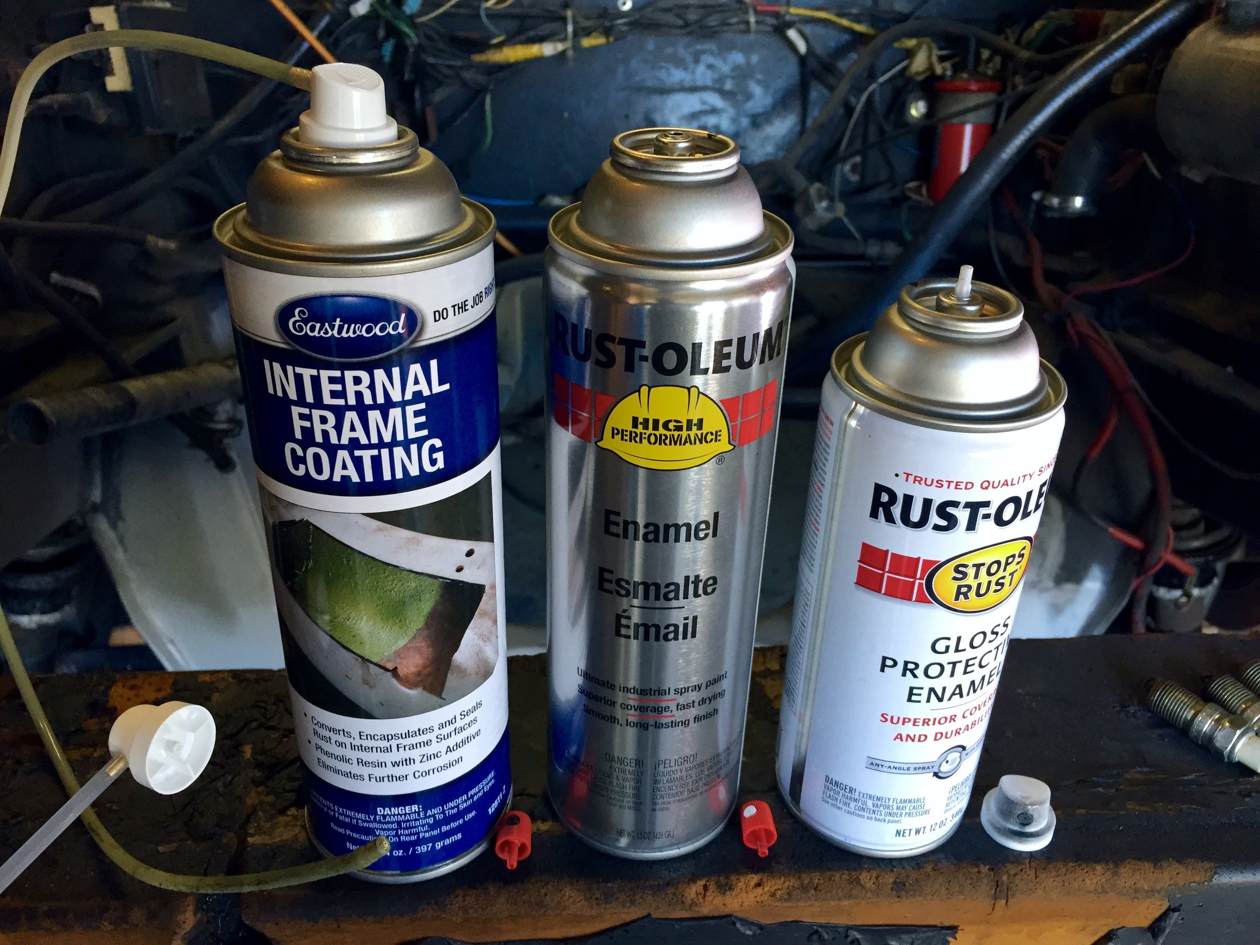 Eastwood Internal Frame Coating and two cans of Rustoleum, with their nozzles removed (each sits next to the base of their respective can in the picture). Notice that the Eastman and grey Rustoleum have red nozzles that stick into their cans, while the white Rustoleum has a larger nozzle that fits onto a tube sticking out the top of the can. The extension wand will only fit on the former style, not the latter.