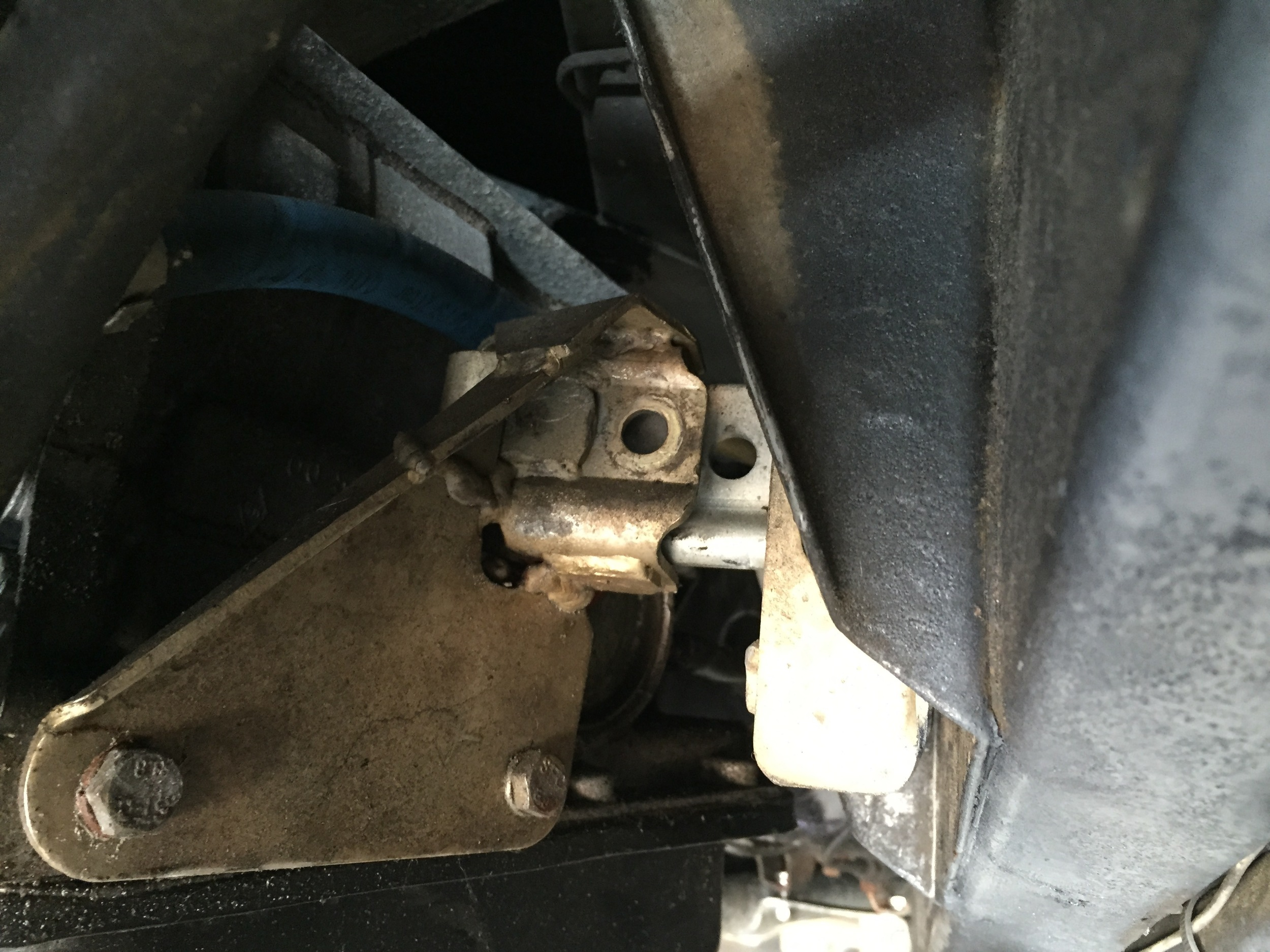 The golden C-like bracket on the transmission mating the mount on the frame behind it. The transmission needs to be shifted a bit to the right so that the holes line up, but otherwise it's in position.