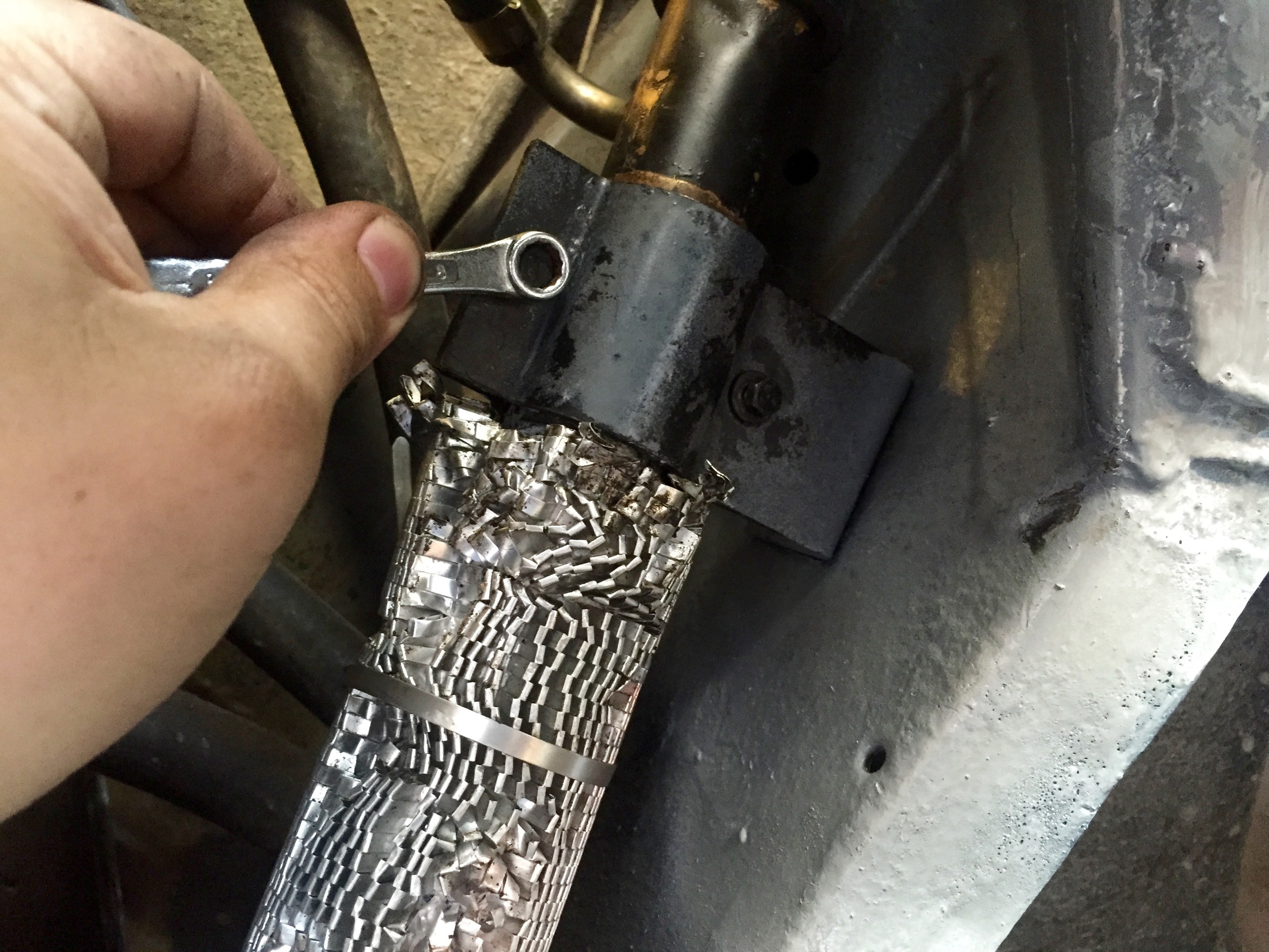 Securing the coolant pipe to the bracket with an 8mm socket.