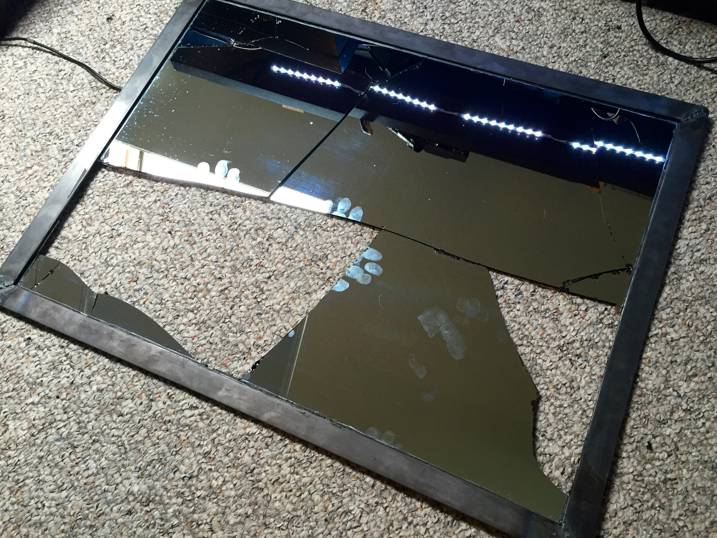 The old shattered mirror glass still attached to the metal frame.
