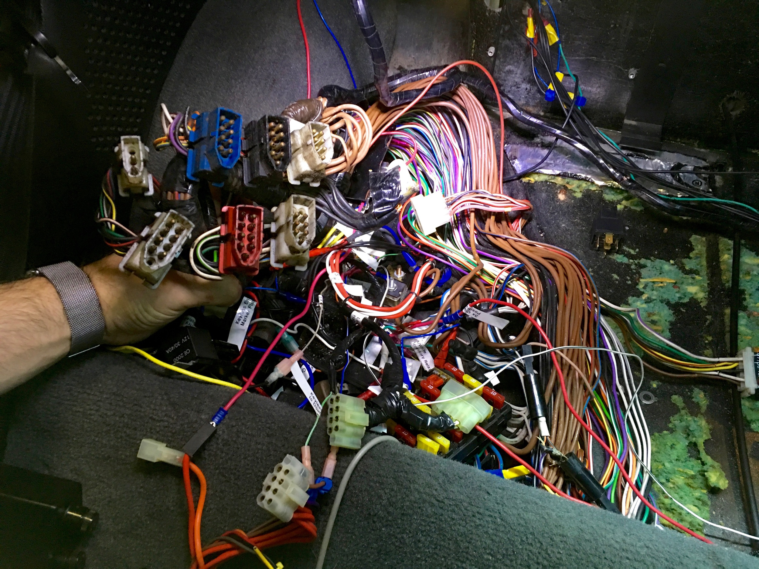 The bundle of liberated bulkhead connectors and unwrapped wiring harness in the relay compartment