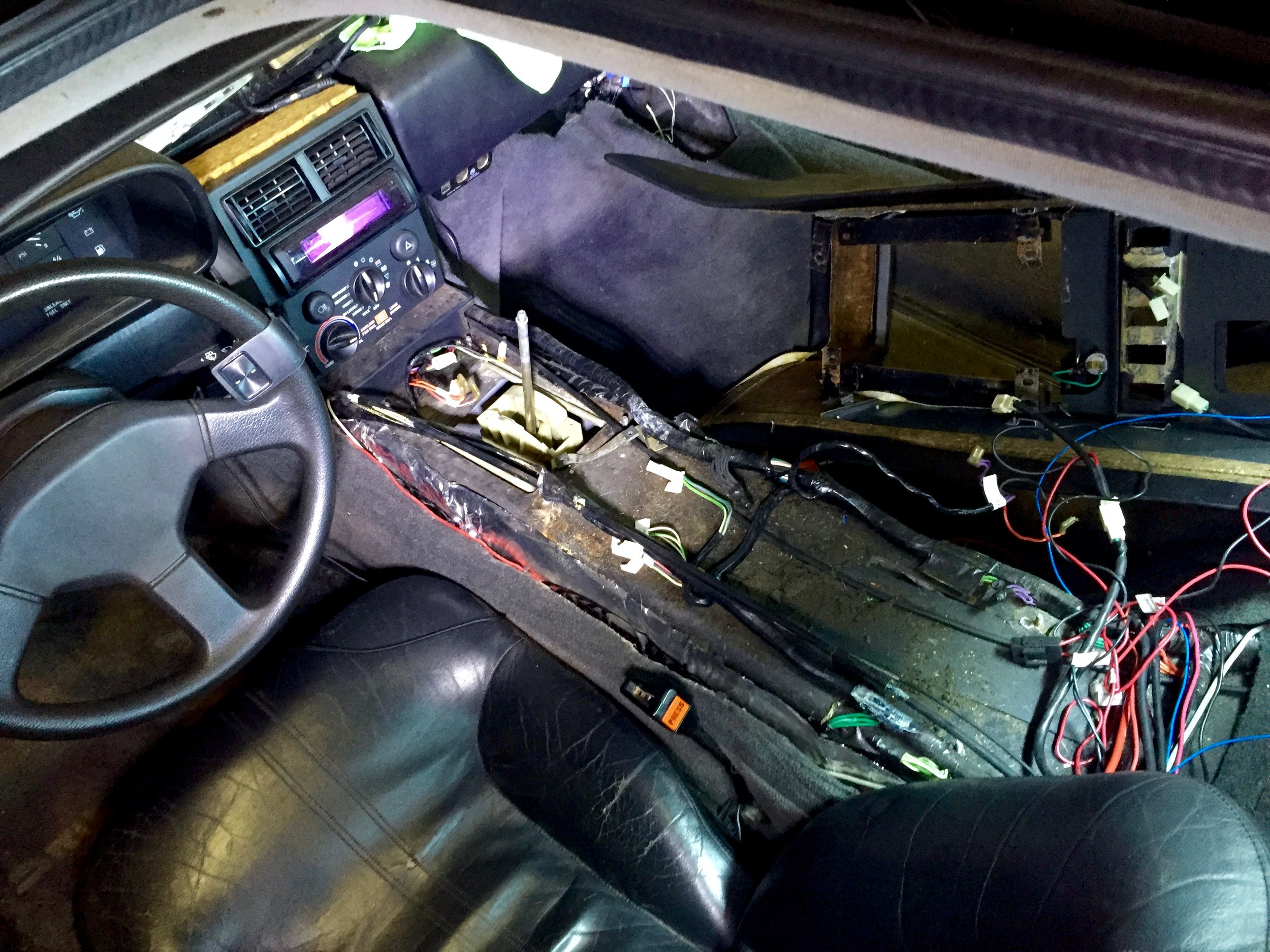 The center armrest completely removed from the car. You an clearly see where the wiring harnesses run on either side of the armrest.