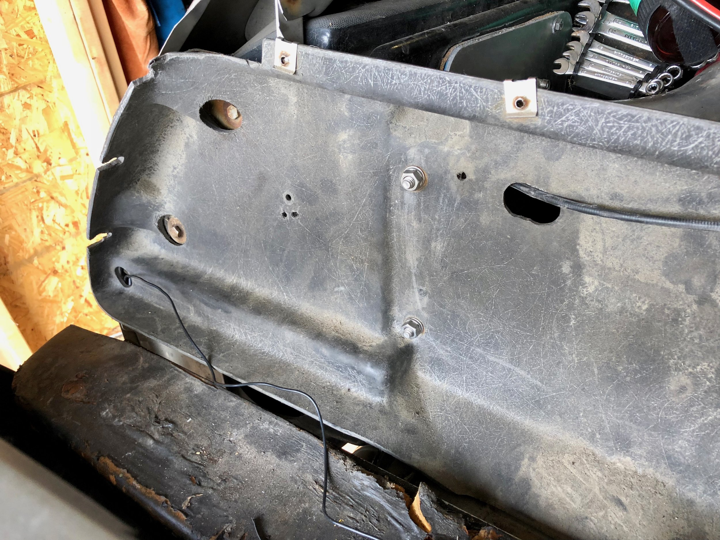 The two nuts and the threads of the bolts that hold the backing to the driver's side can be seen in the center of the picture.  The cluster of three holes is where one screw goes through the backing into the fiberglass.  The cable on the right is for the engine cover latch.