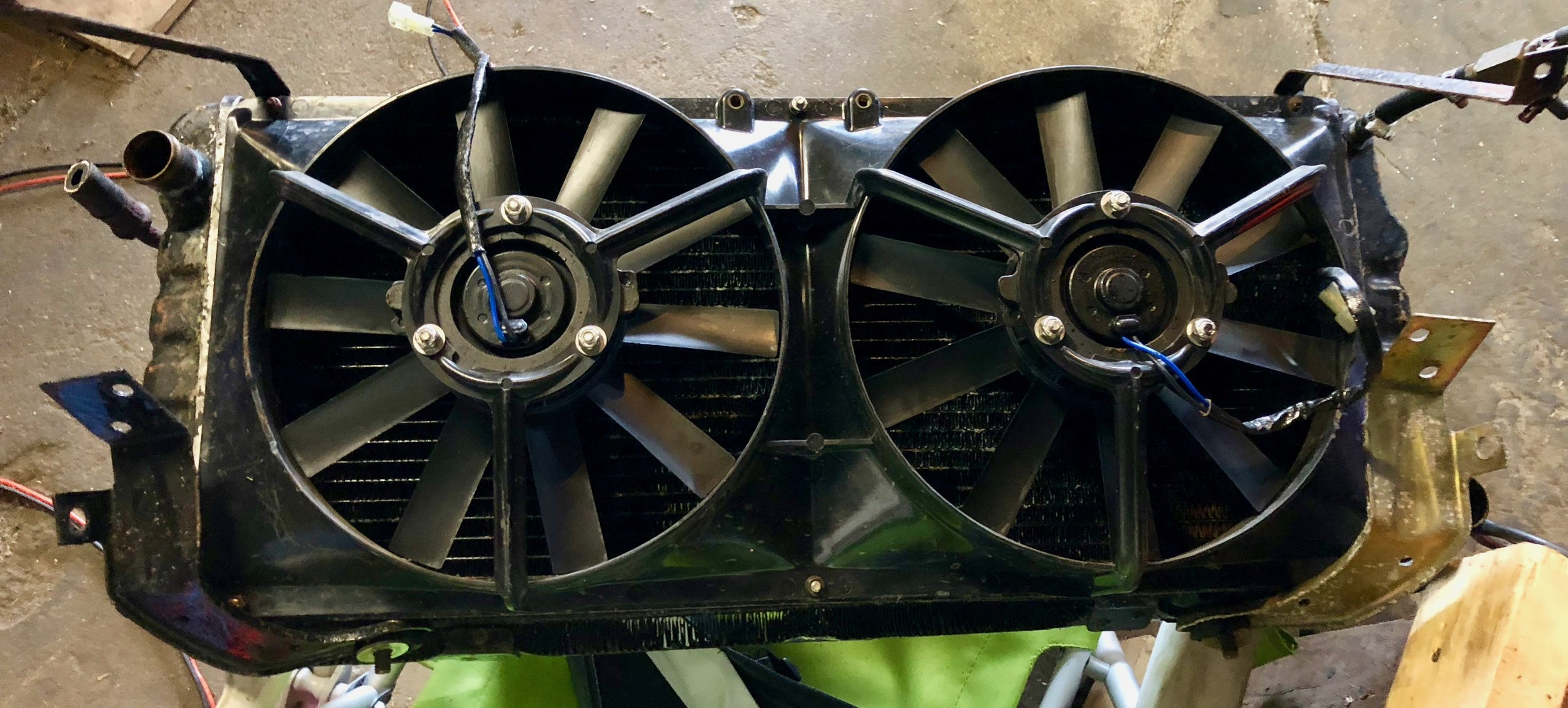 The radiator, condenser and fans removed from the car. The angled braces are still attached to the top of the radiator.