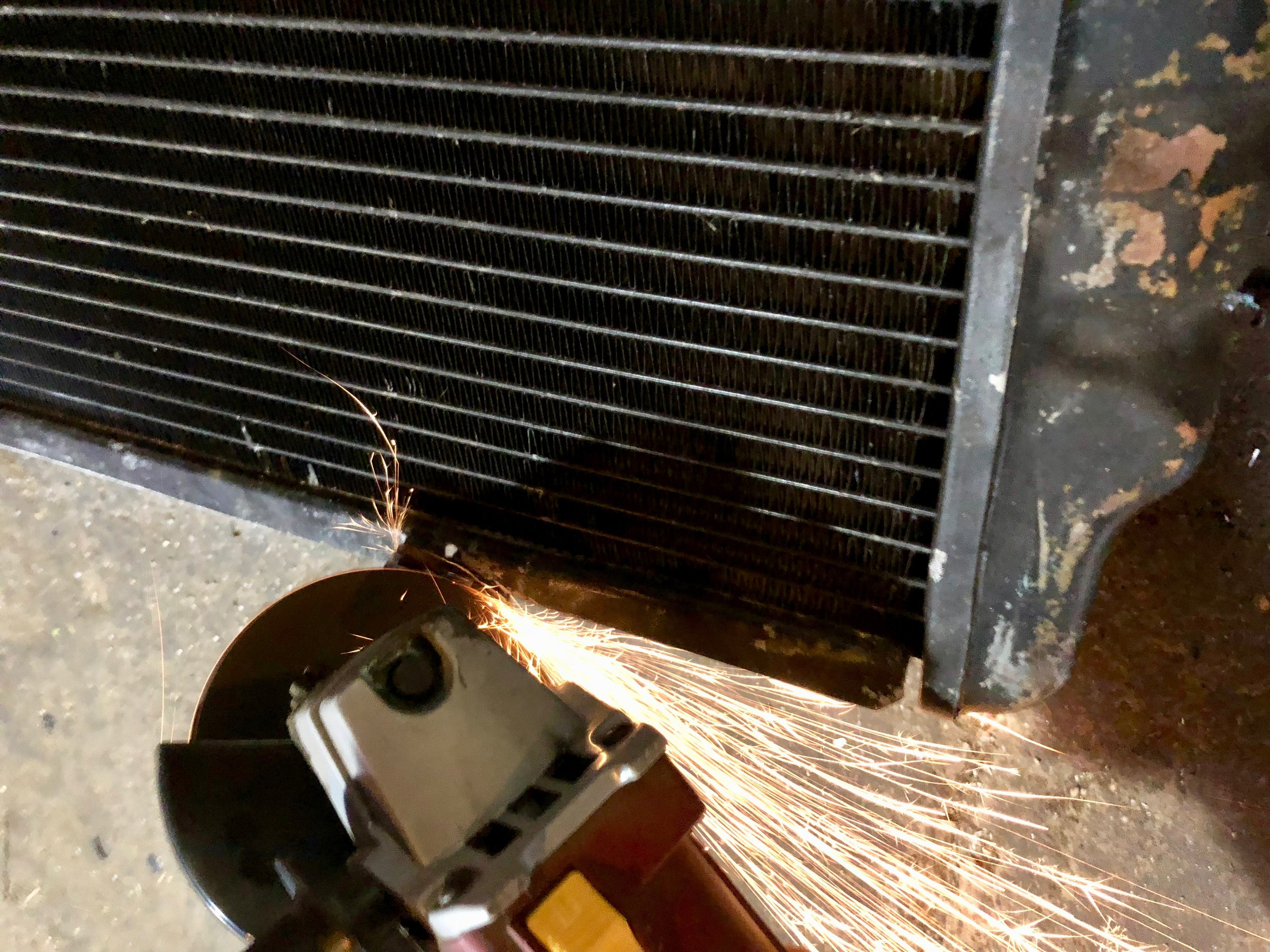 Grinding the broken condenser brackets off of the radiator.