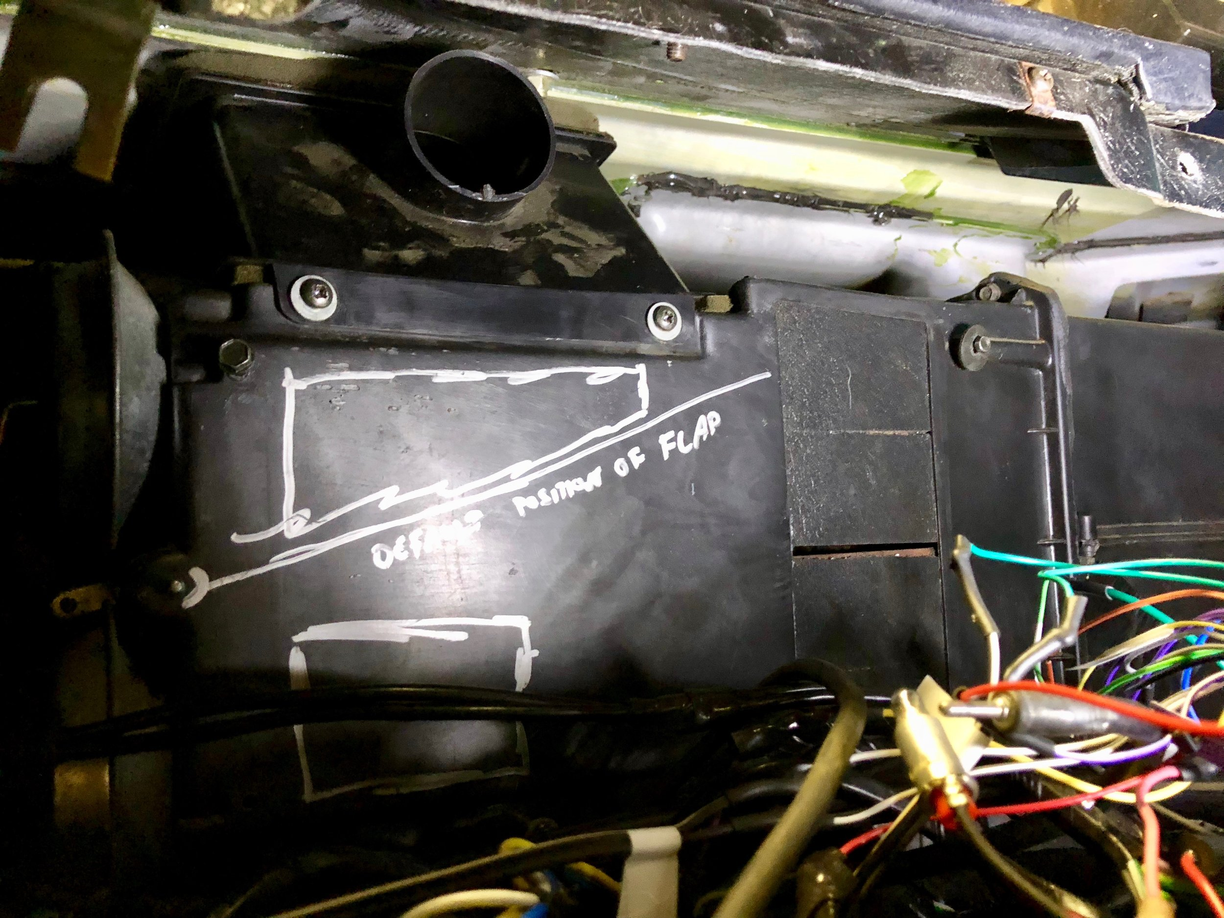 The position of the defrost vent under the dash. The two screws on the face come out, and then it can be tilted out from under the dash. The air distributor is removed in this picture, as is the duct that goes from the distributor to the vent. The drawings on the box are for a later experiment, and indicate safe areas to cut the box and the default location of the defrost flap.