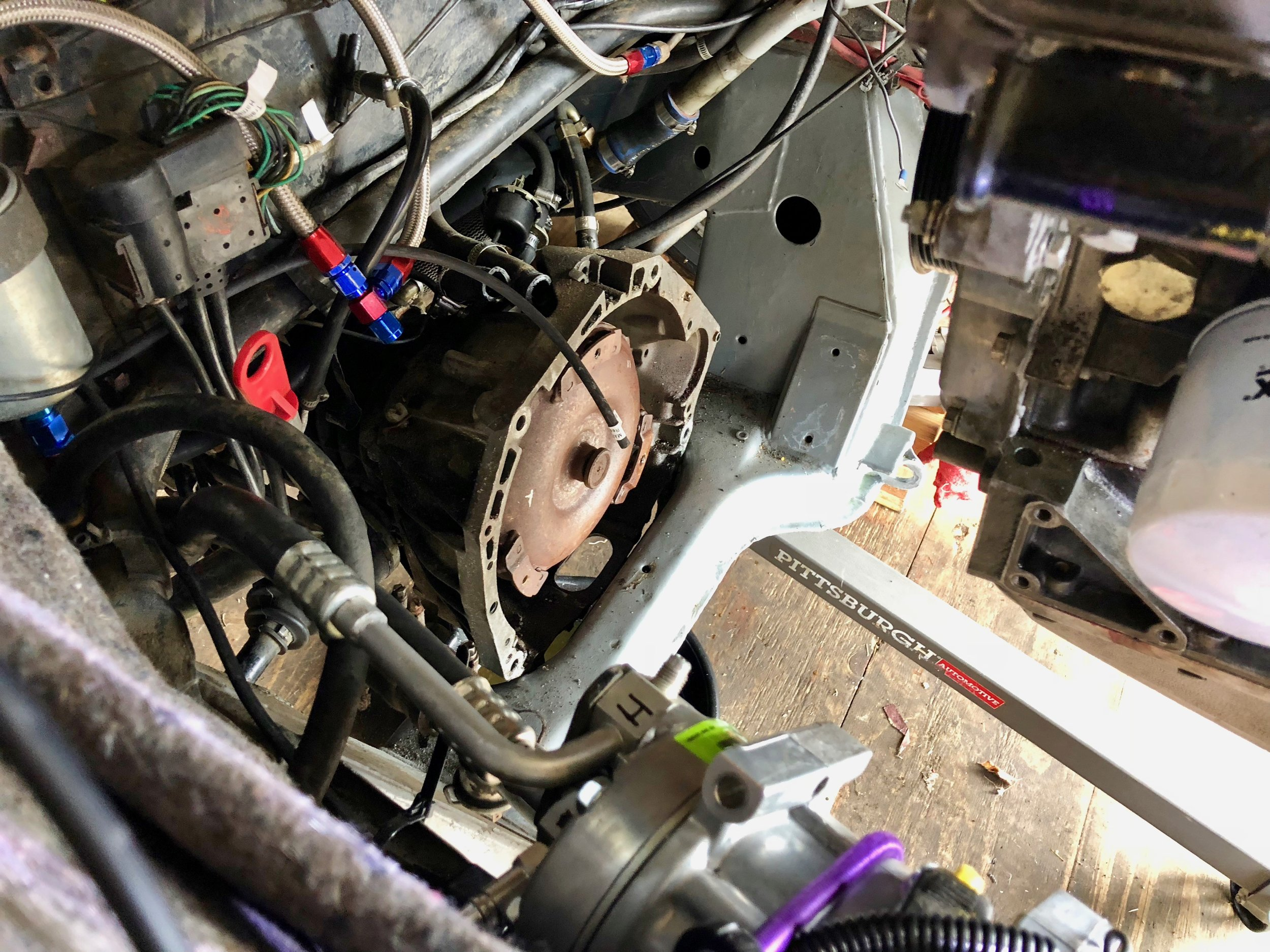 The separated transmission resting against the edge of the engine subframe.