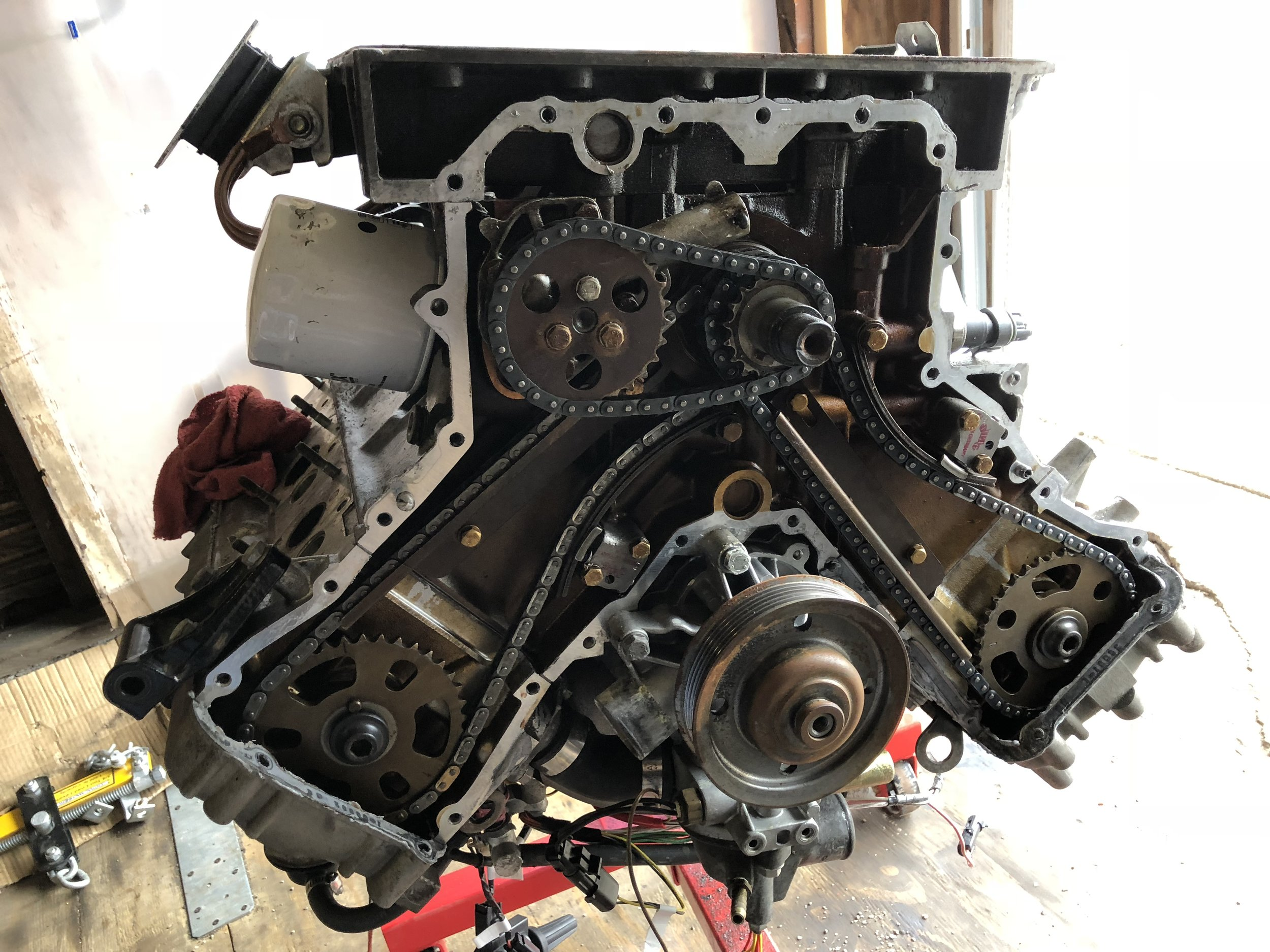 The upside down engine with the timing cover removed. The oil pump is still mounted behind its sprocket.