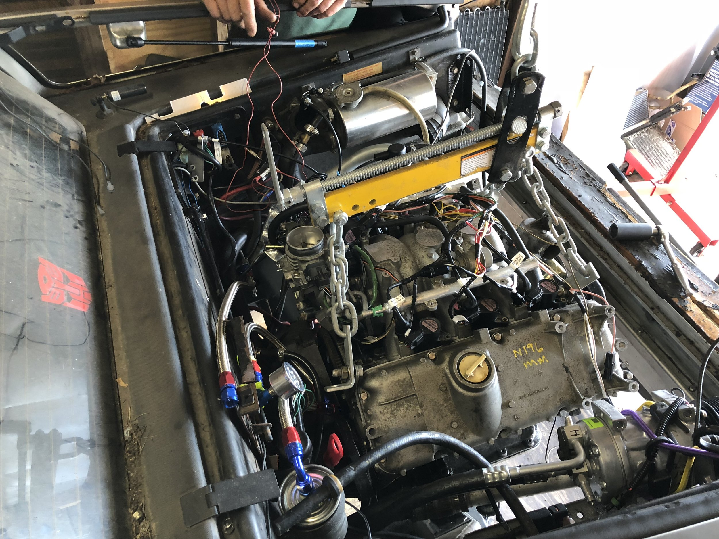 The engine lowered back into the engine bay. The flex plate can be seen as the engine isn't yet aligned to the transmission.