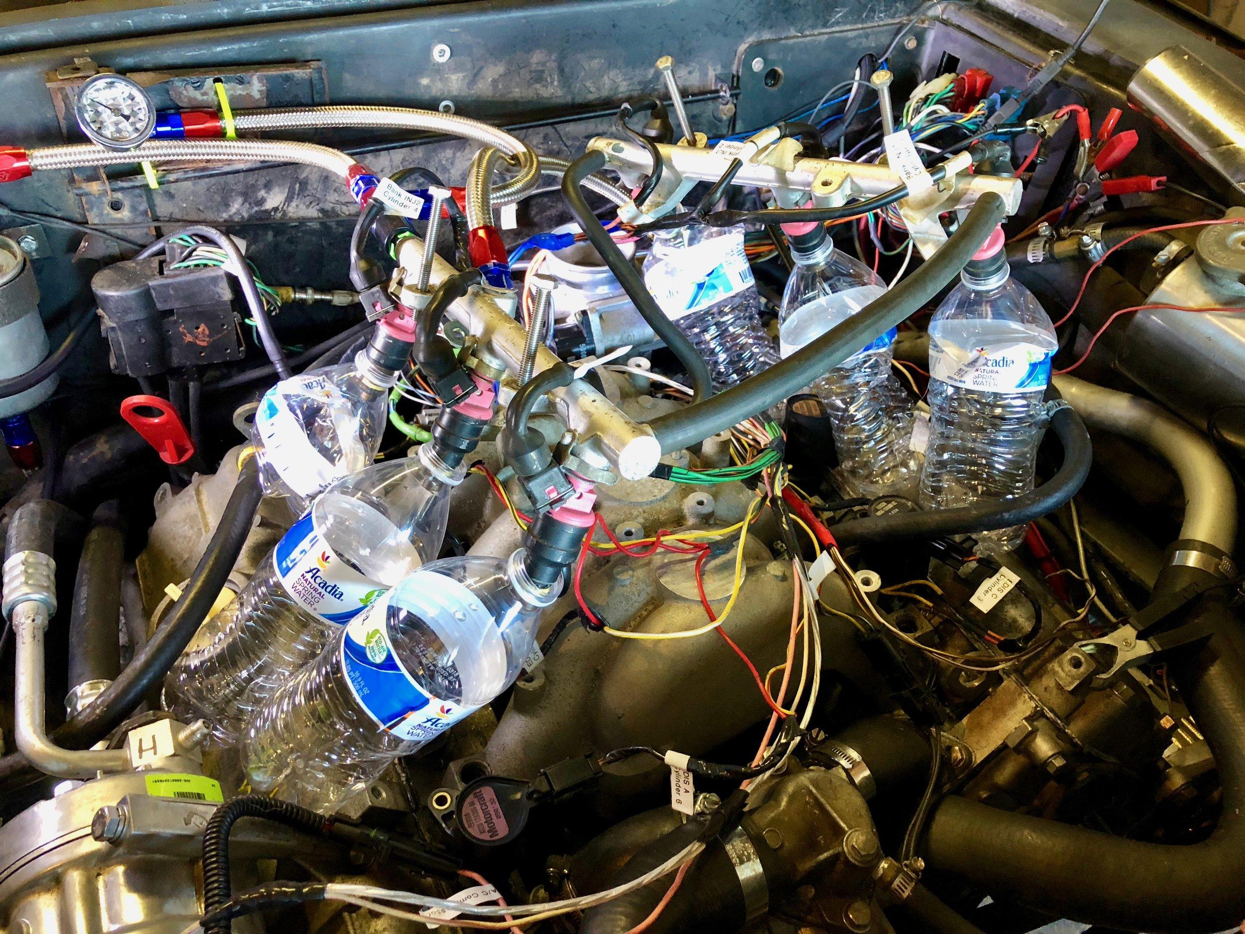Injectors in water bottles for testing fuel flow.