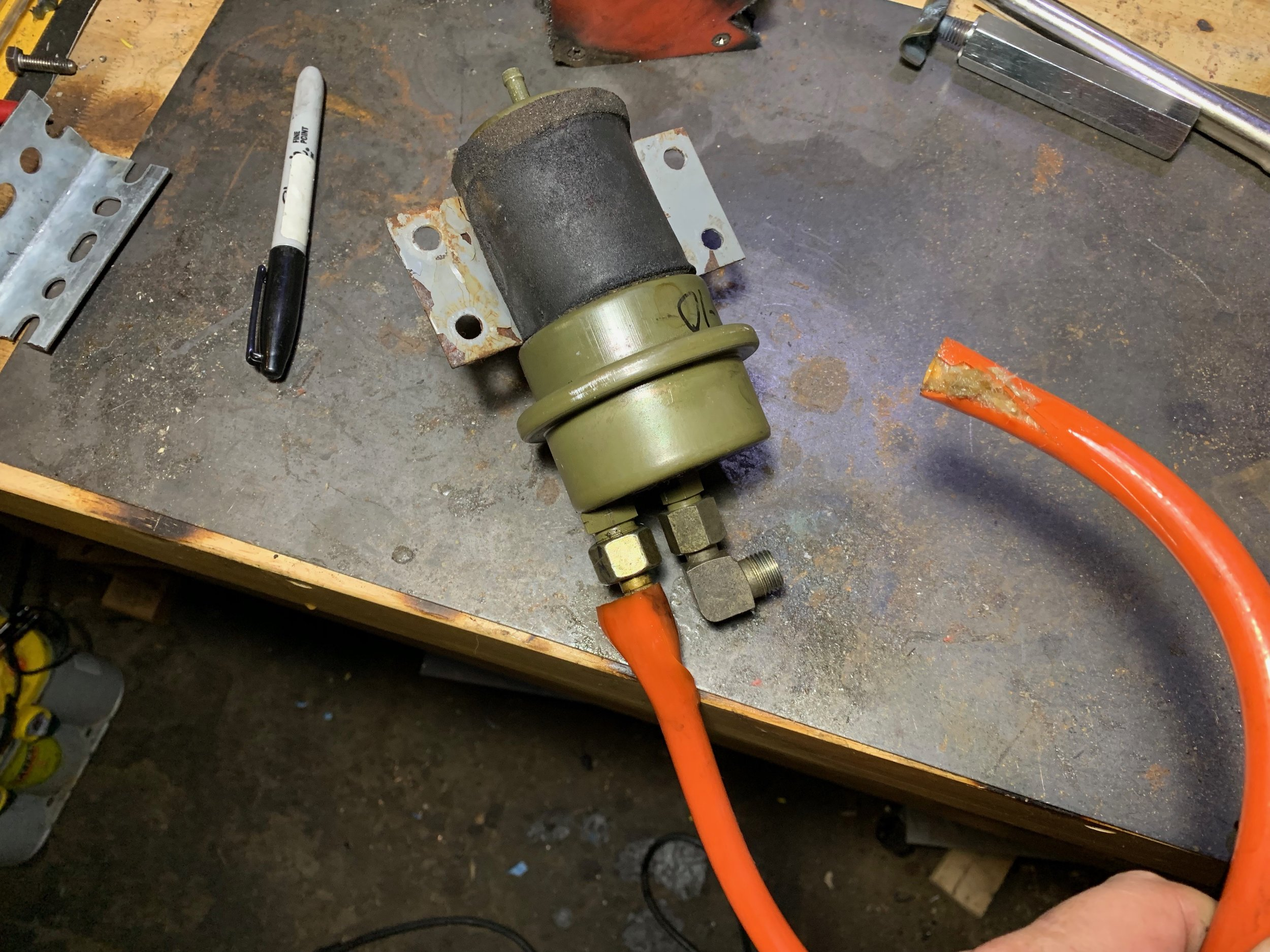 The accumulator removed from the car. One end of the orange hose is partially cut for removal, while the other end was cut off in the car.