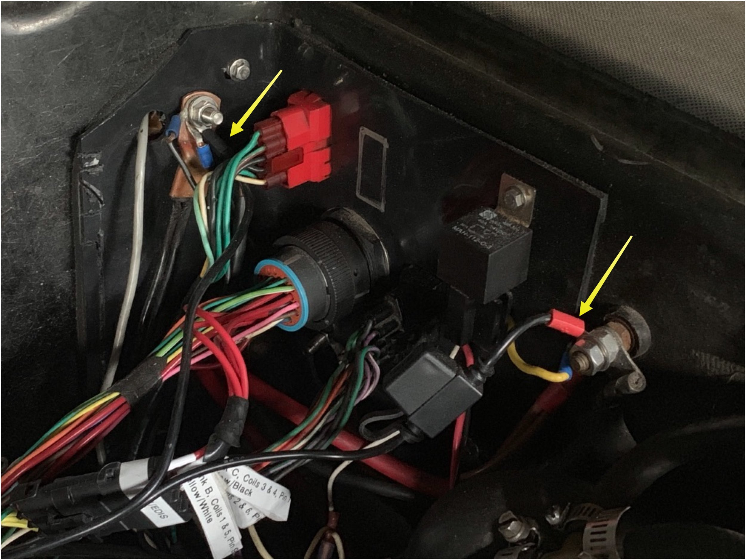 The battery charger's plug connections to in the engine bay. The positive lead has an inline fuse, and the connector has a cap. When not in use the wire is tucked along the rail on the firewall.