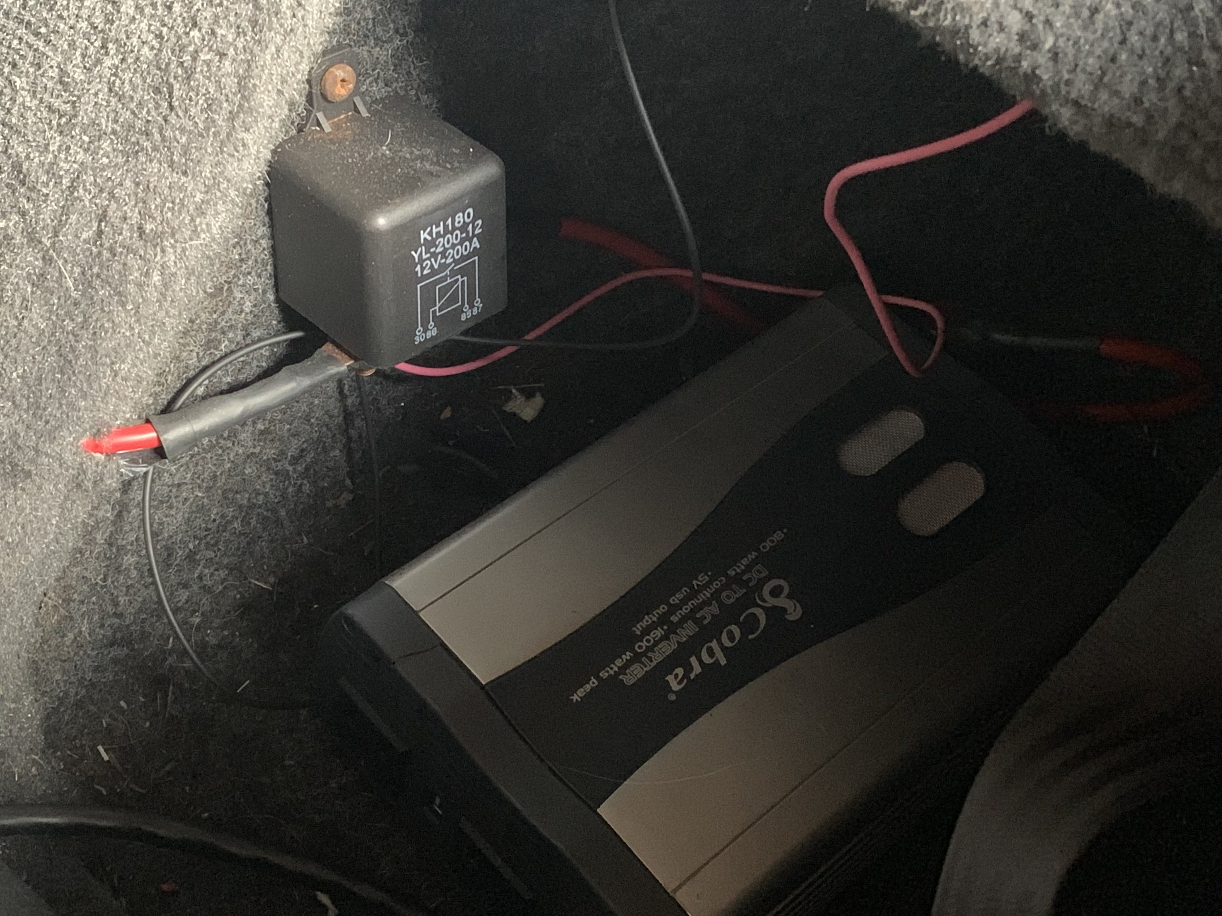 The 200A relay screwed into the lock box behind the driver's seat. One of the large red wires goes directly to the battery, while the other goes to the inverter. The smaller wires run to an ignition-switched fuse box behind the passenger seat. The inverter's ground goes directly to the battery.