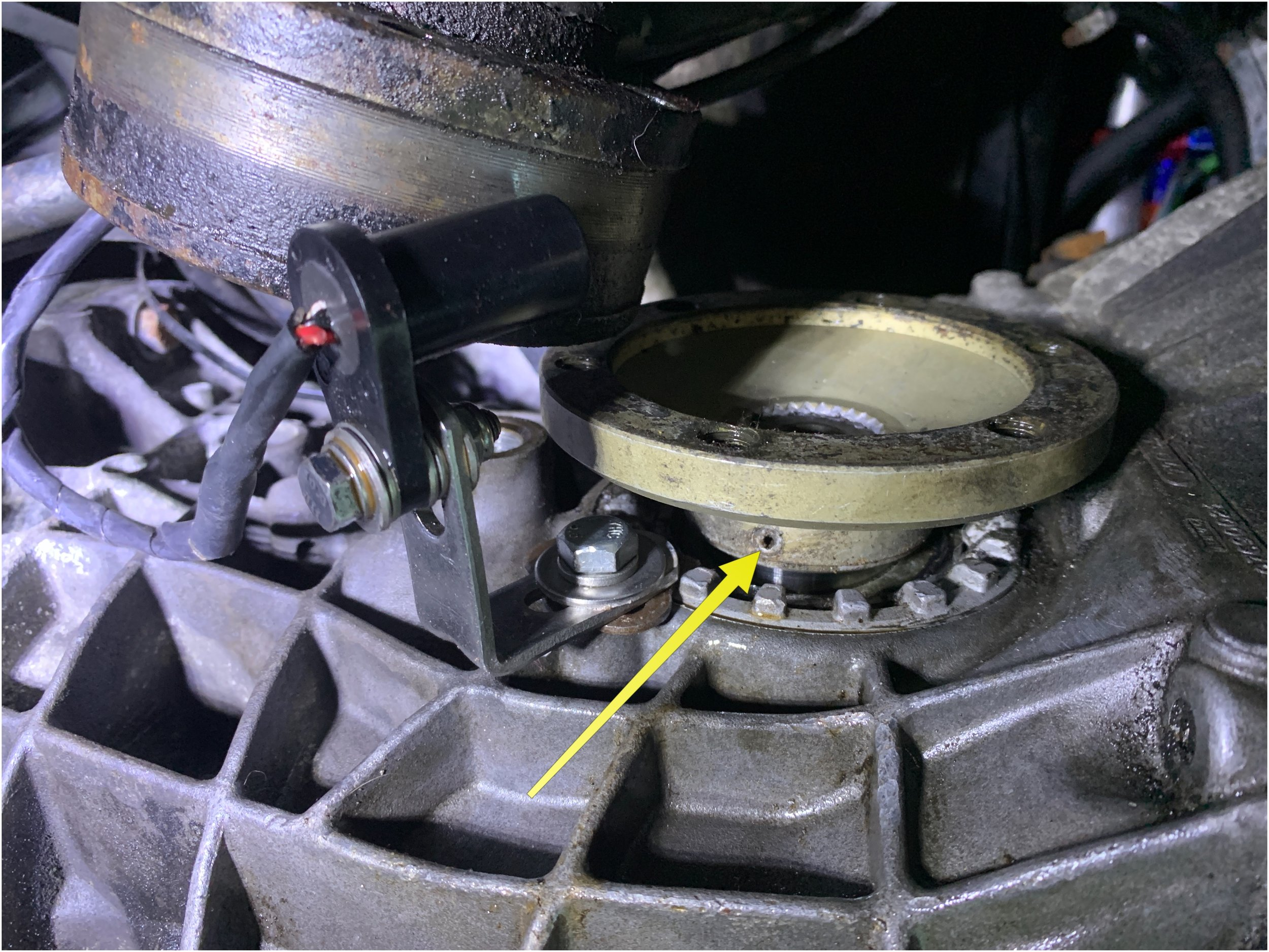 After unbolting the axle, the roll pin has to be tapped out with a 6 mm punch. Make sure the flange is rotated so that the pin won't get stuck against the transmission case once it is mostly tapped out.