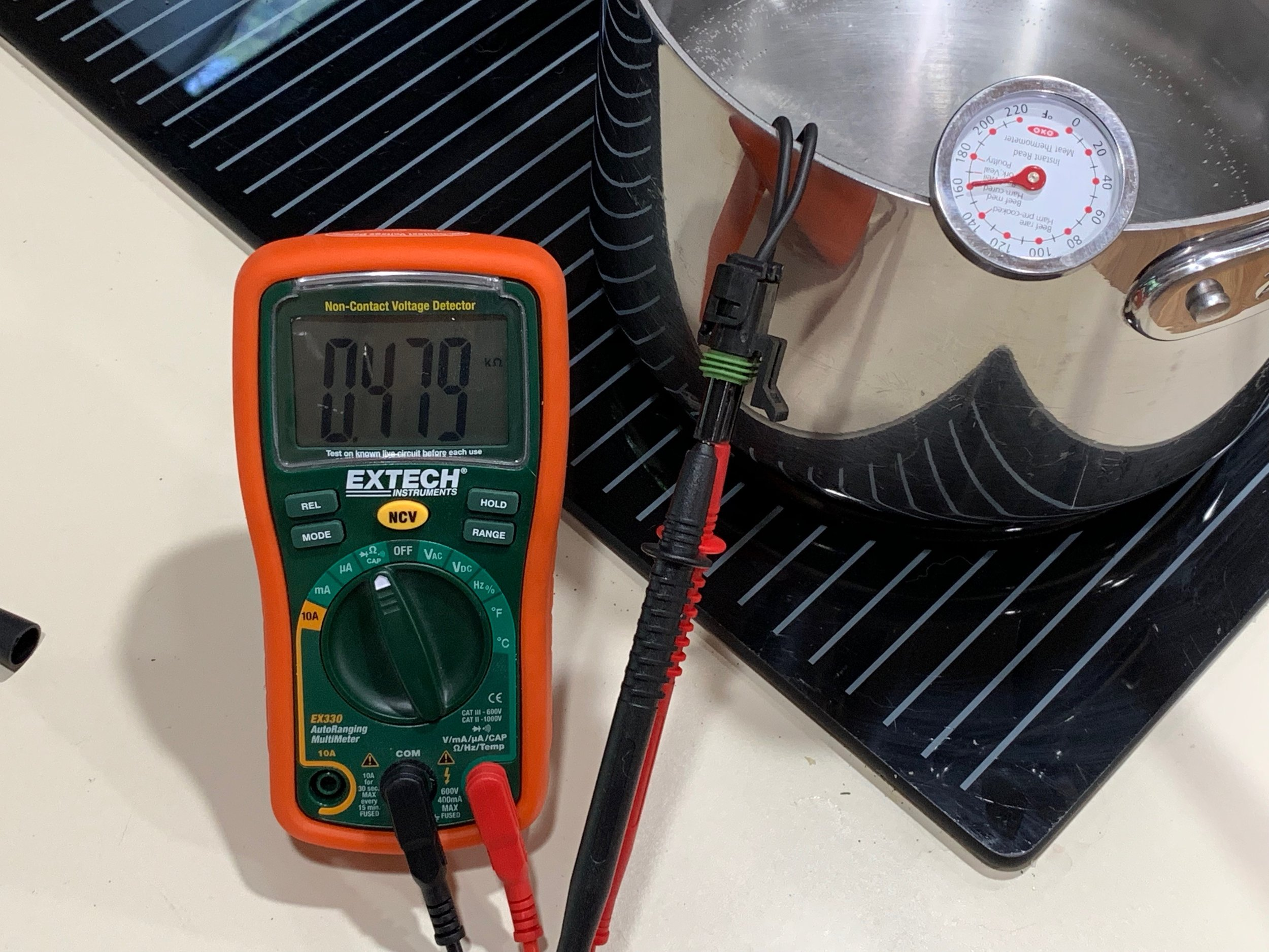 Using a thermometer, an ohm meter and a pot of boiling water to calibrate the high end of the coolant temperature sender.  In this picture the sender is still warming up.  Only the end of the sender is in the water, not the whole thing.  Also, the meat thermometer would read differently depending on how much of it was in the water, so I'm not sure how well I did my calibration here.  The ice water and room temperature readings were much easier (I forgot to take pictures of those).