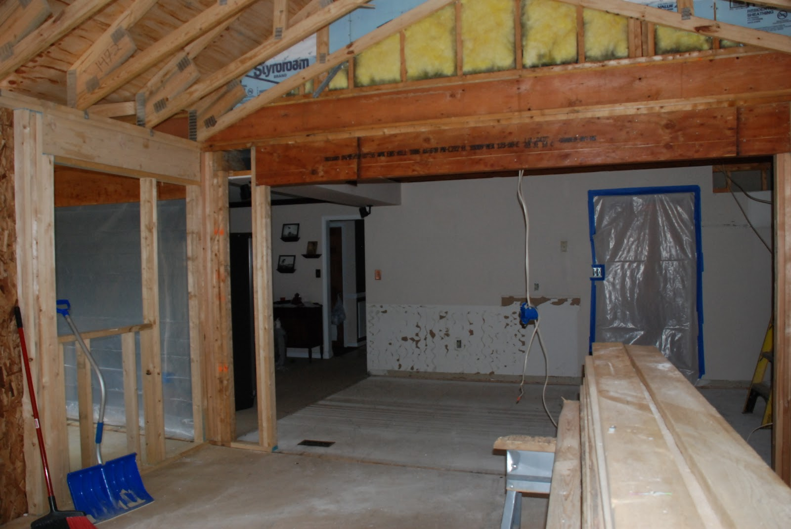 During:  looking into the original kitchen from the new breakfast room, the entire back wall of it has been removed.  The second story is now supported by a dropped engineered lumber beam.