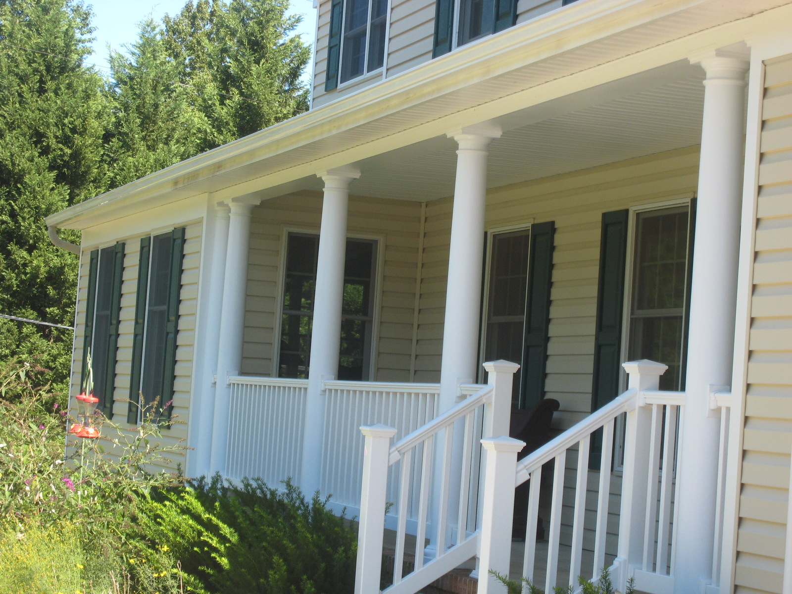 """After: the existing porch roof plane extends over the front of the new addition. The porch columns and rails were also redesigned to avoid the """"toothpick"""" effect of too-small posts."""