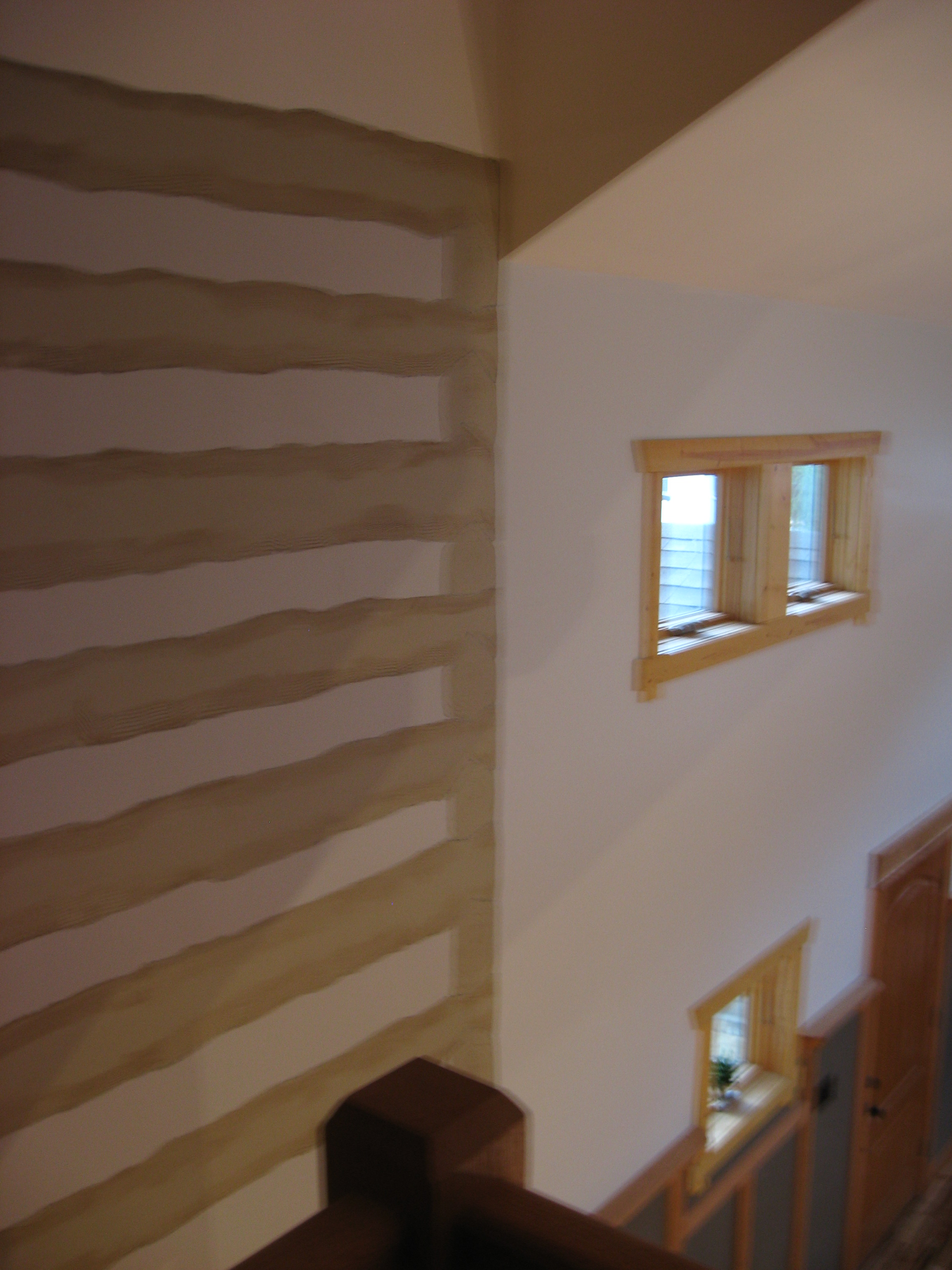 After:  the homeowner, an artist, painted this drywall to resemble the existing logs inside of it.