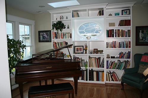 This sweet elliptical window is visible from the stair hall. Windows to the left of the piano look to the water.