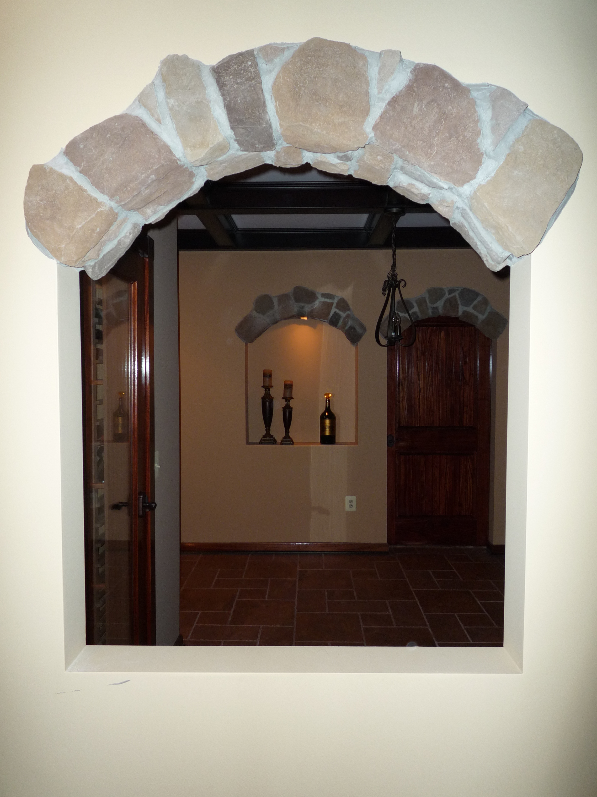 "The door in the wall beyond leads to unfinished basement.  To mimic this arch beside the bottom of the existing basement steps, I thickened that wall beyond in order to design a 3-1/2"" deep display niche the same shape and size as this one.   Symmetry achieved inside the wine-tasting room."