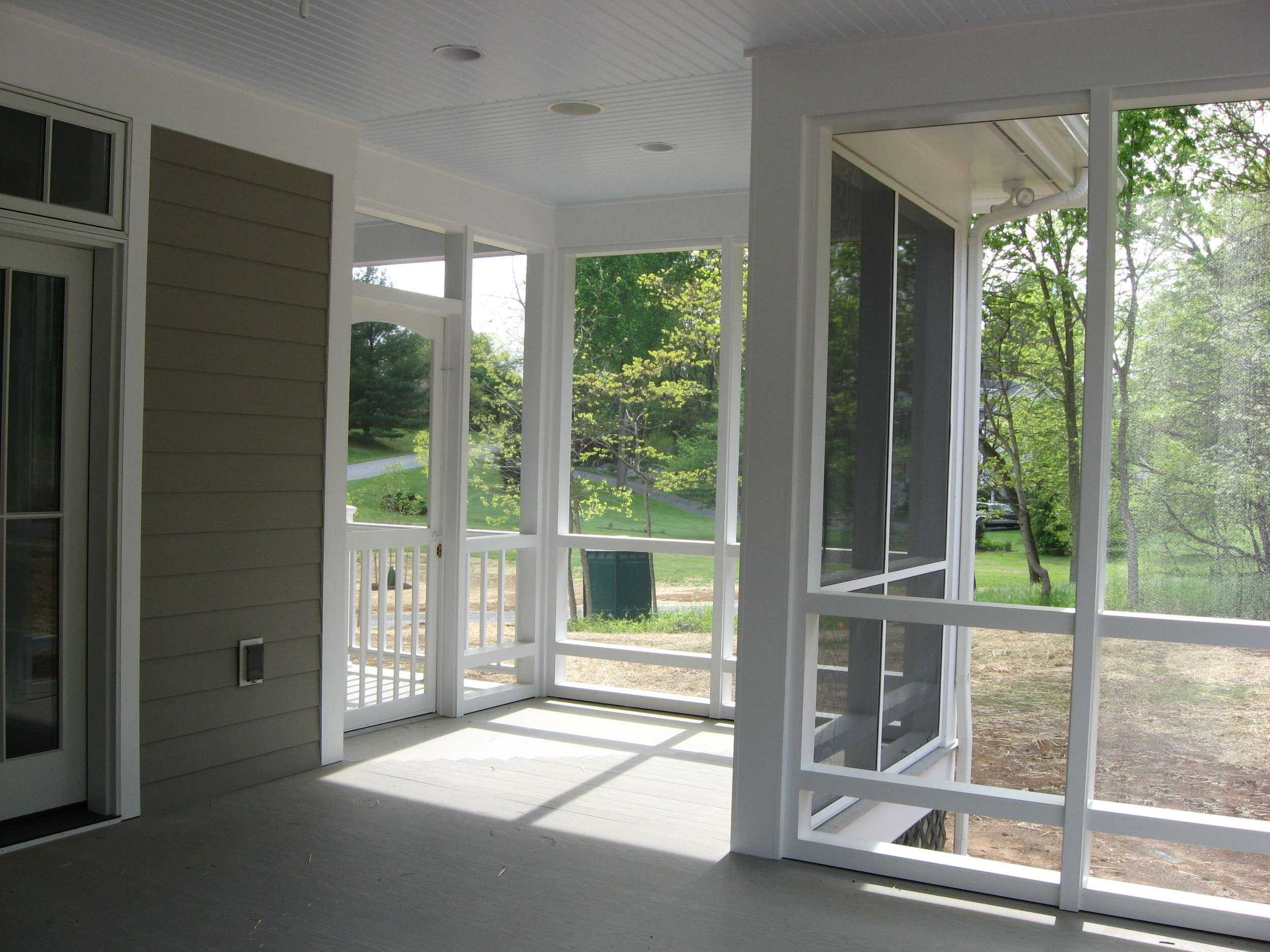 The rear porch is screened but the side and front porches are not.  Continuity of the porch flooring, porch depth, and repeated columns ensure a smooth transition from one space to the other.