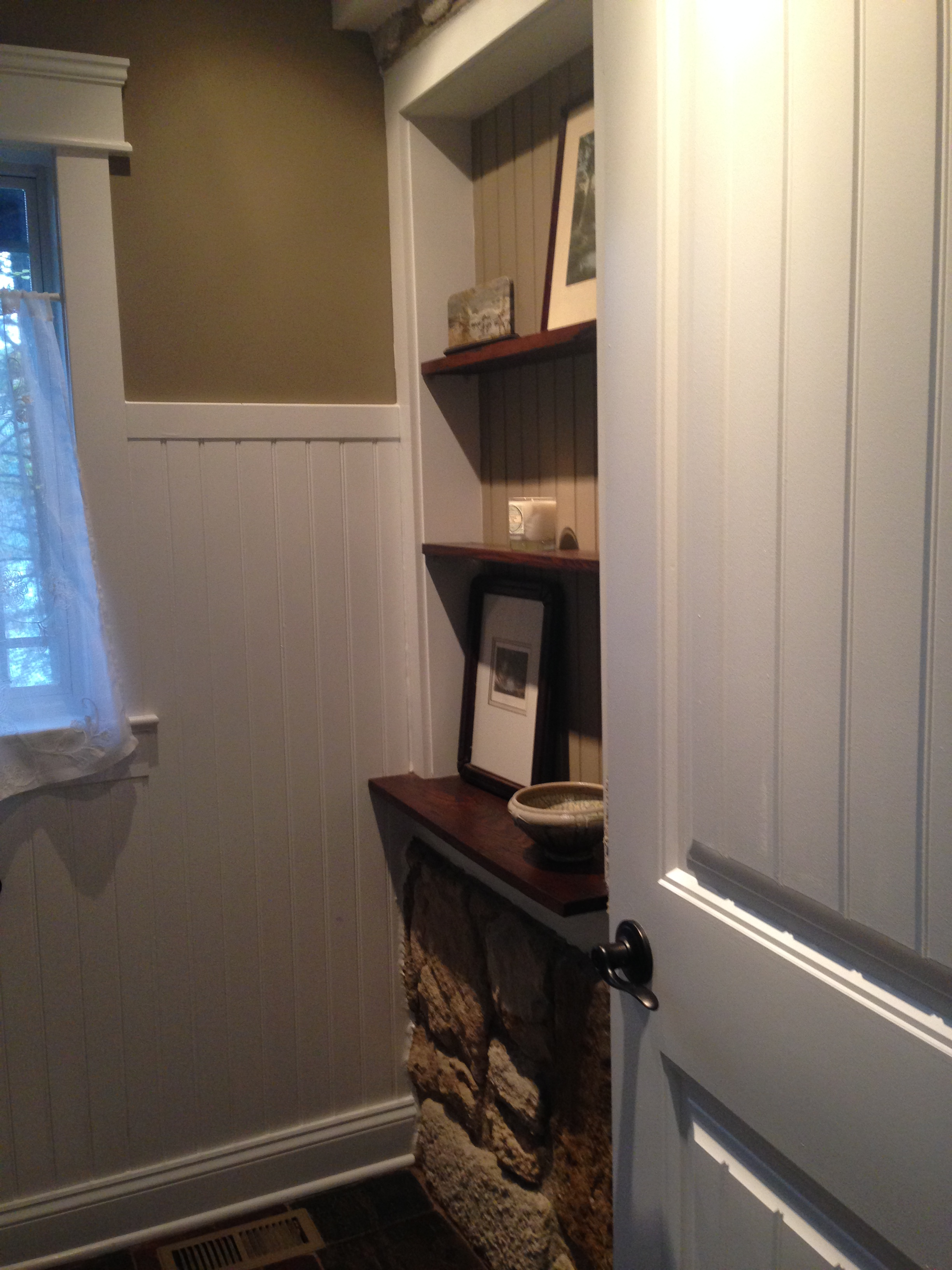 The builder/owner worked wonders with this original window opening, which is now in the new powder room and serves as a beautiful display niche opposite the toilet.