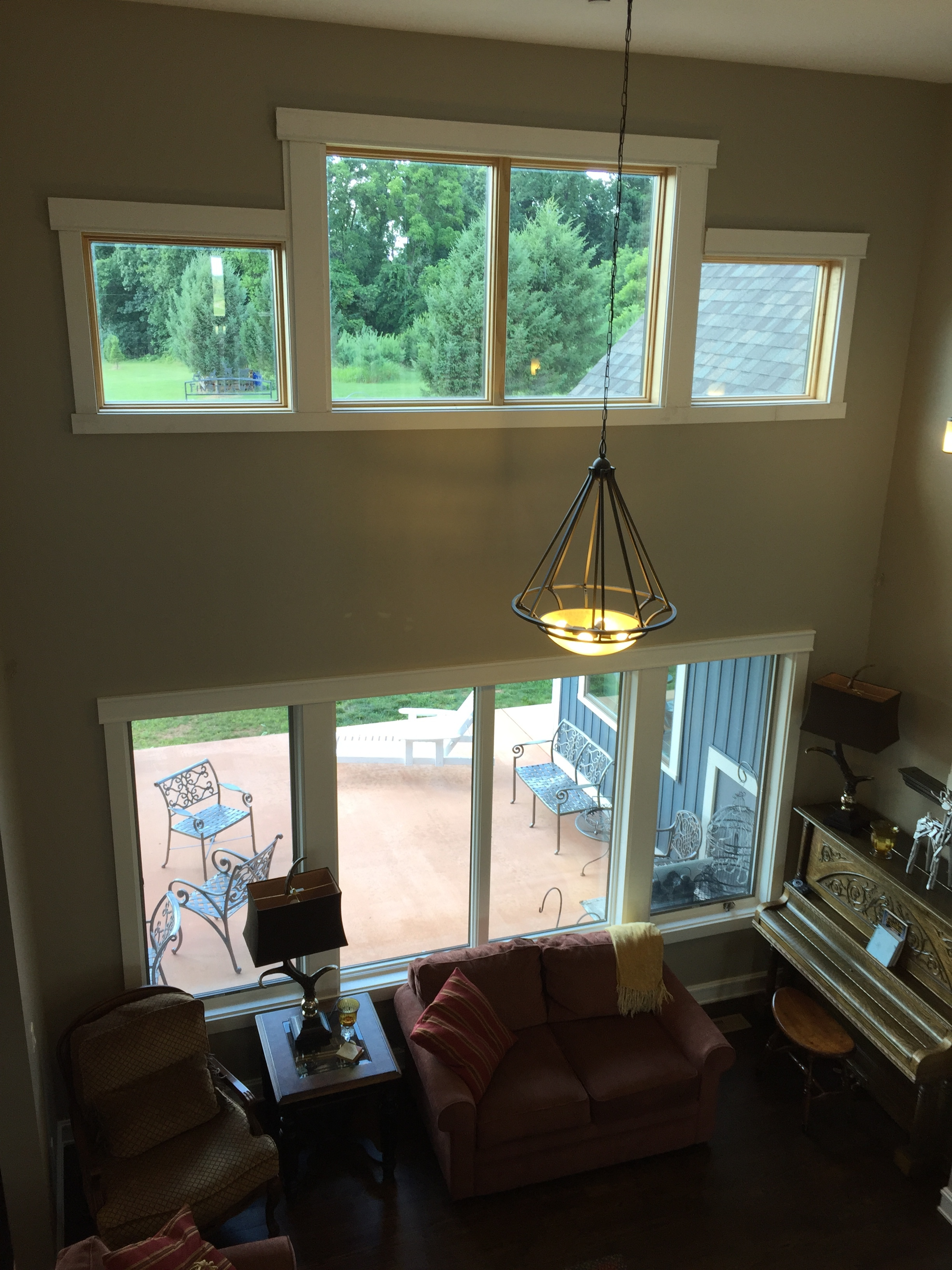 The windows of the two-story living room are spaced apart vertically to fit a patio shed roof between the upper and lower units.