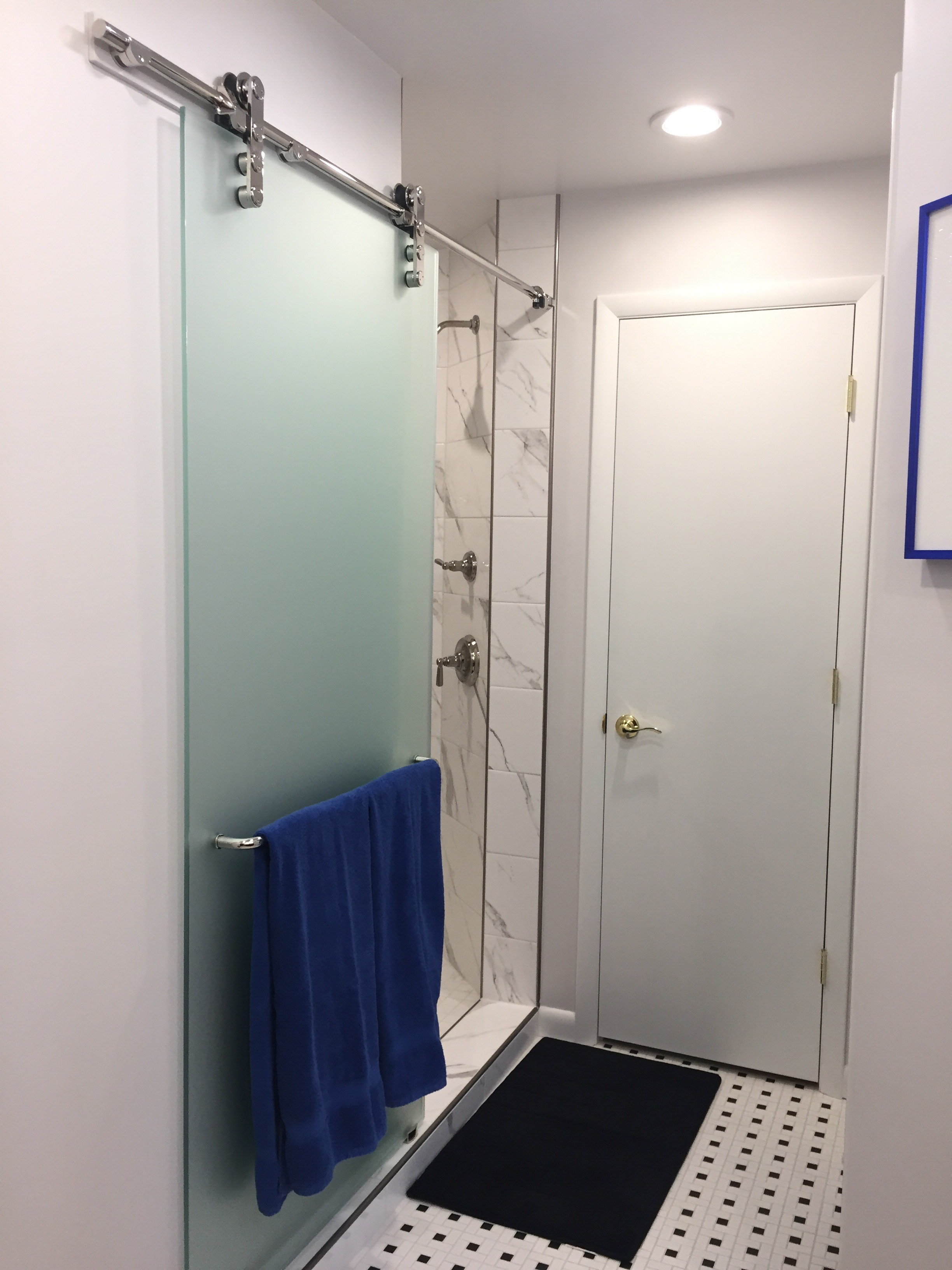 """After, a large shower's door is mounted on contemporary barn door hardware to keep it out of the way. A new linen closet is at the end of the bathroom. The door to the toilet is out of sight, just to the right (opposite the shower). One of the old living room windows is in the toilet's compartment now, for a great view of the private wooded back yard while """"thinking""""."""