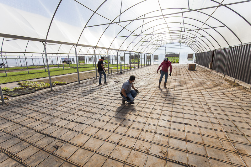A new hot water heated floor is installed in a greenhouse at Johnson's Backyard Garden, Austin, TX.